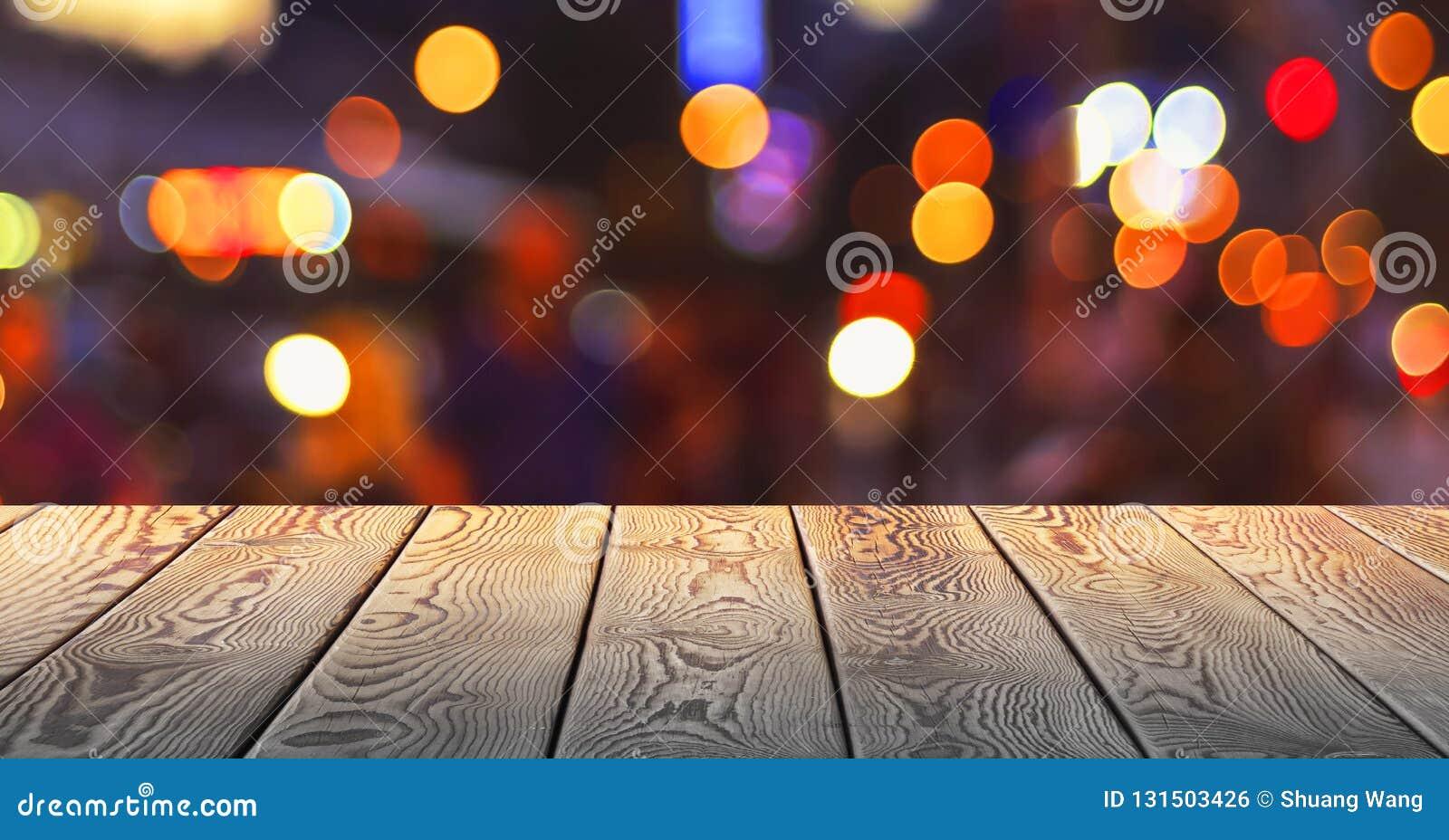 Концепция рождества: Праздничная предпосылка со светлыми пятнами и bokeh перед пустым деревянным столом