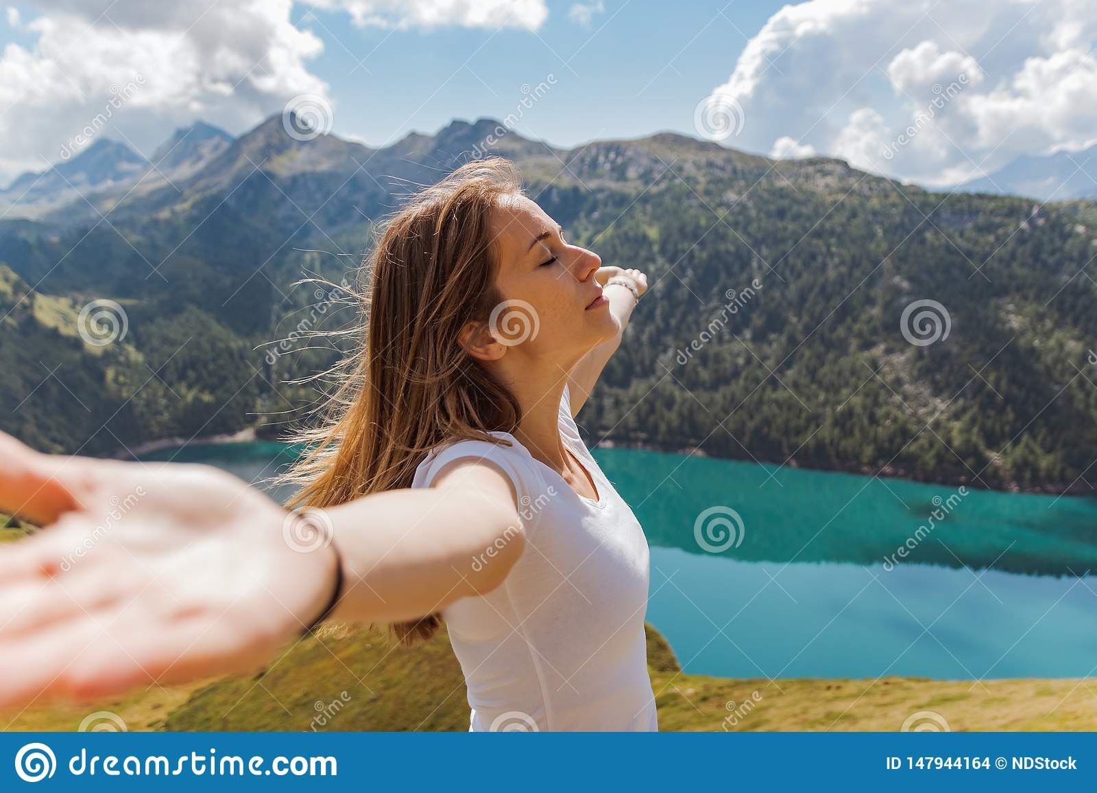 Концепция свободы молодой женщины с ее поднятыми оружиями наслаждающся свежим воздухом и солнцем