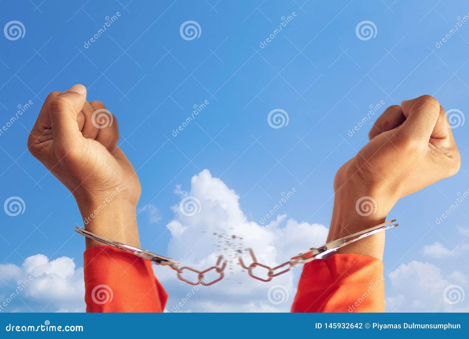 Концепция свободы 2 руки пленника со сломленным наручником для свободы знача с голубым небом на предпосылке