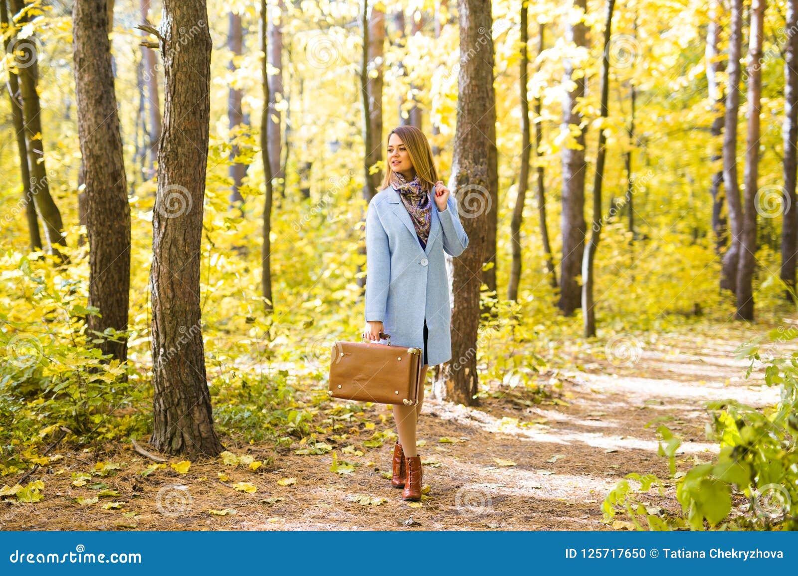 Концепция сезона, природы и людей - женщина в парке осени стоя с чемоданом