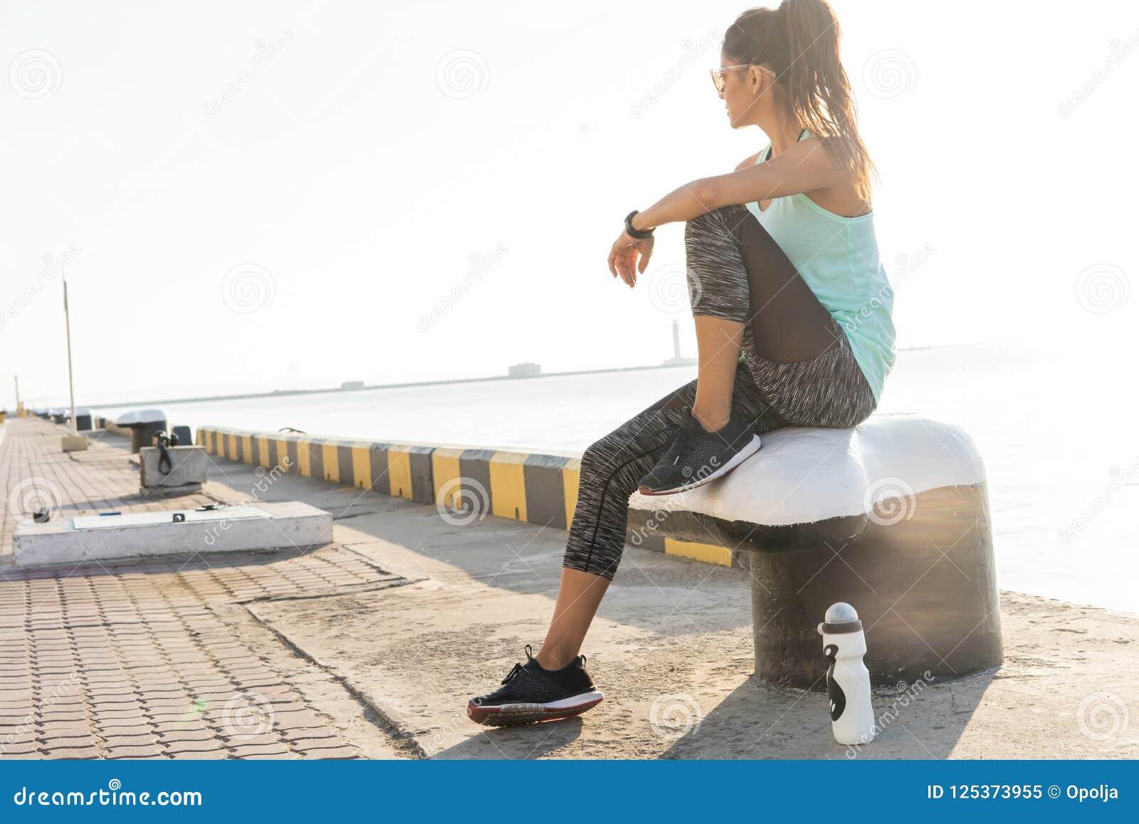 Концепция спорта и образа жизни - женщина отдыхая после делать резвится outdoors