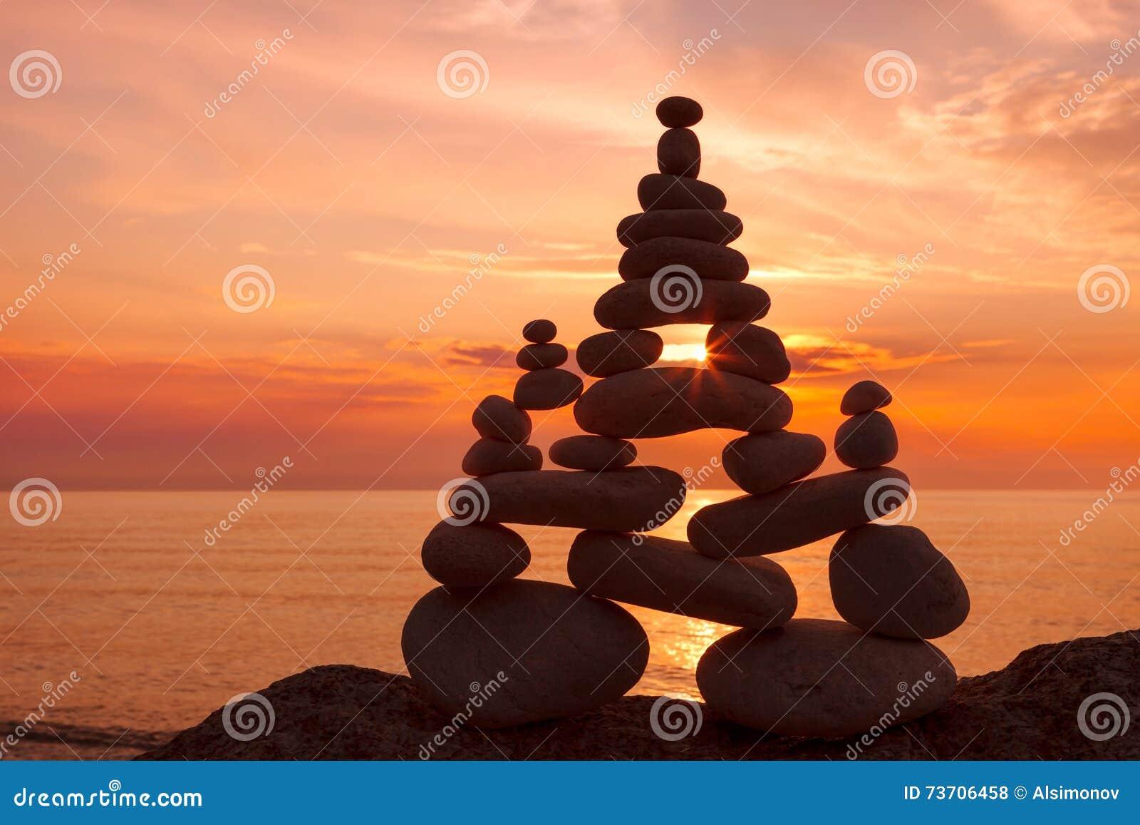 Концепция сработанности и баланса Дзэн утеса на заходе солнца
