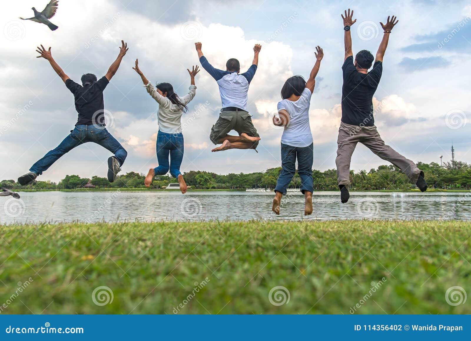 Концепция успеха сыгранности с группой в составе скача друзья в общественном парке