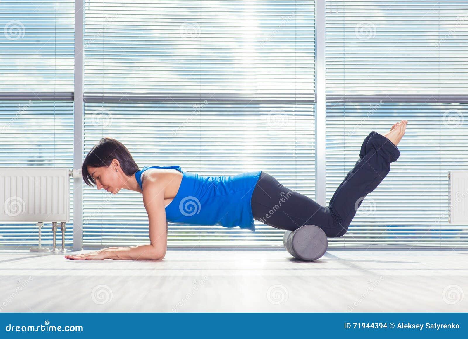 Концепция фитнеса, спорта, тренировки и образа жизни - женщина делая pilates на поле с роликом пены