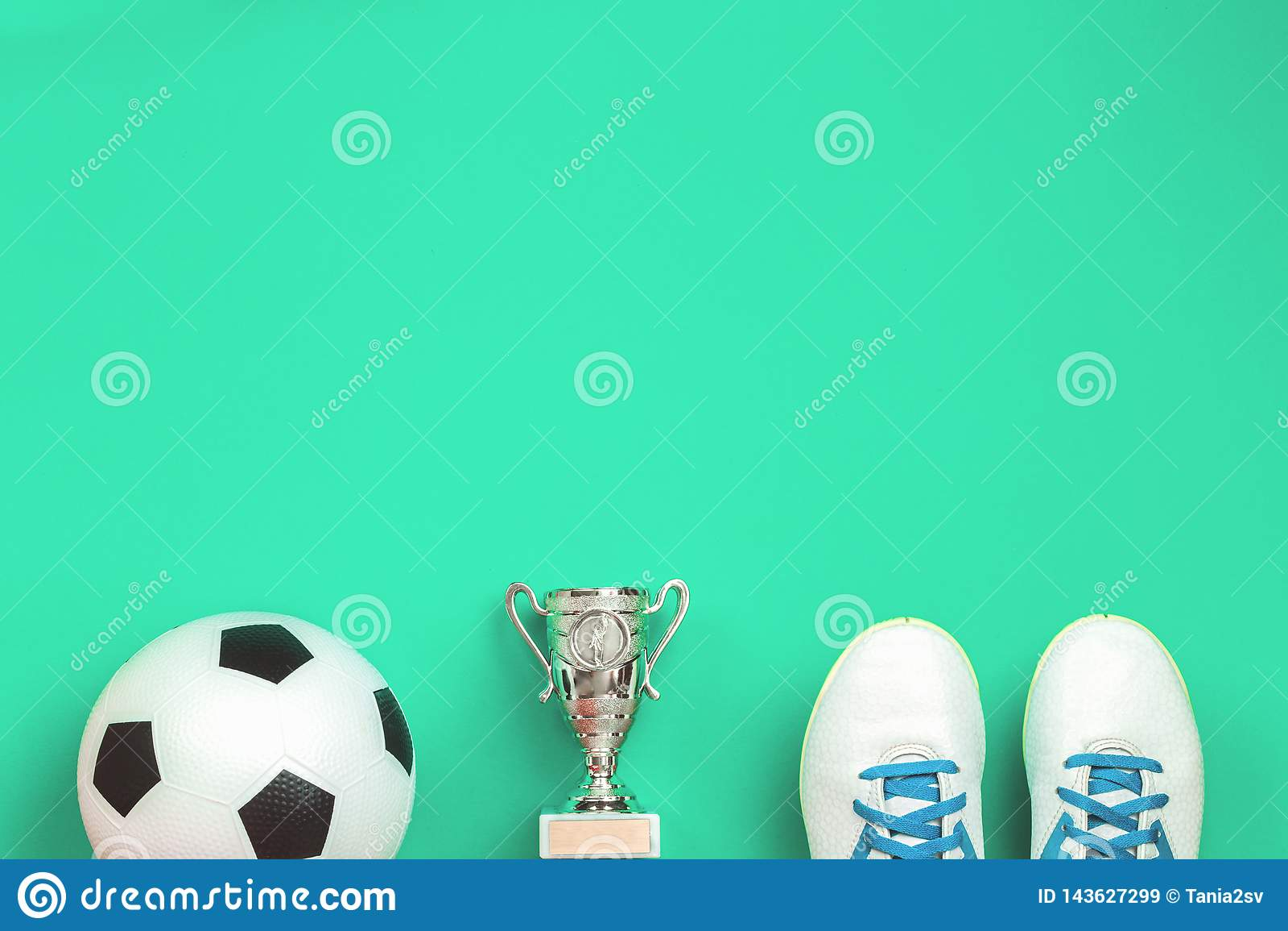 Концепция футбола с ботинками, чашкой и шариком футбола
