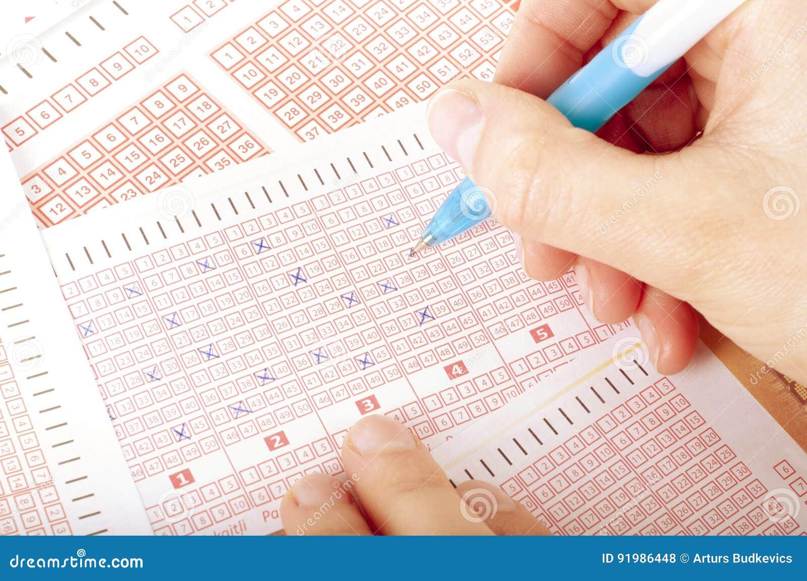 Концепция Succes - номер маркировки руки ` s персоны на билете лотереи с ручкой
