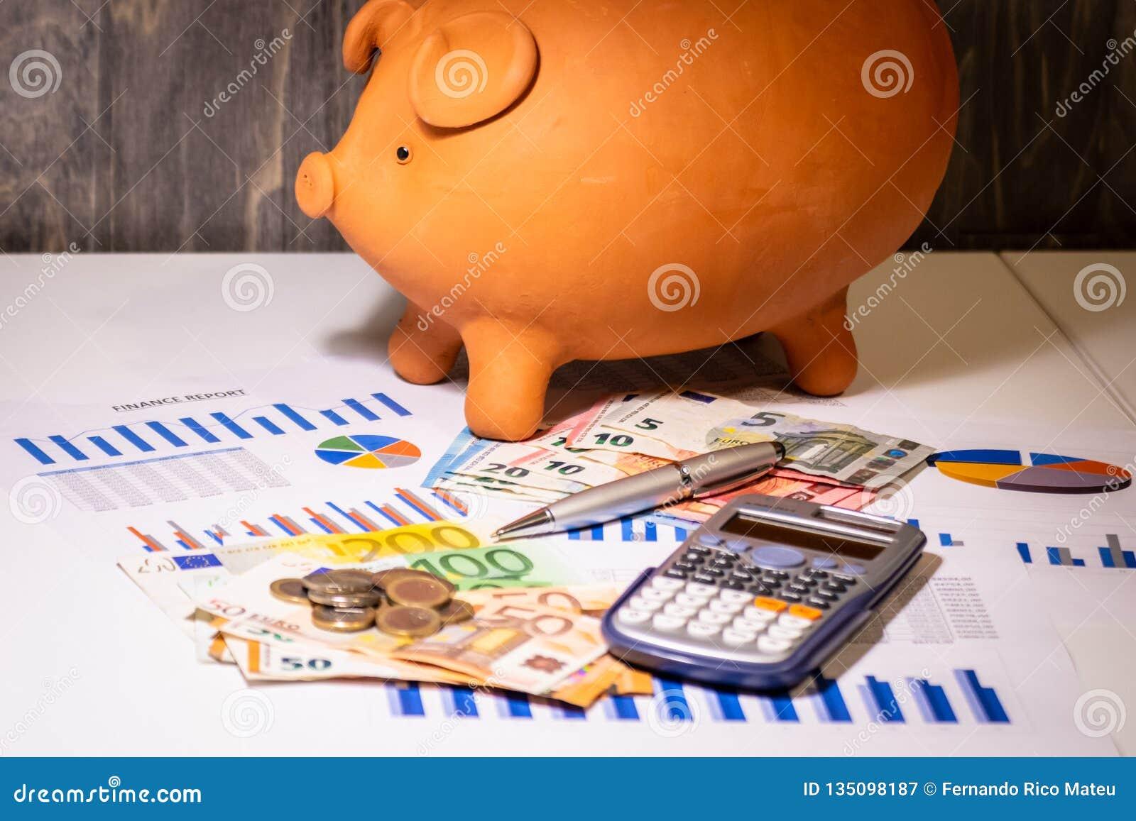 Копилка на деньгах, счетах евро, бизнес-отчетах, ручке и калькуляторе