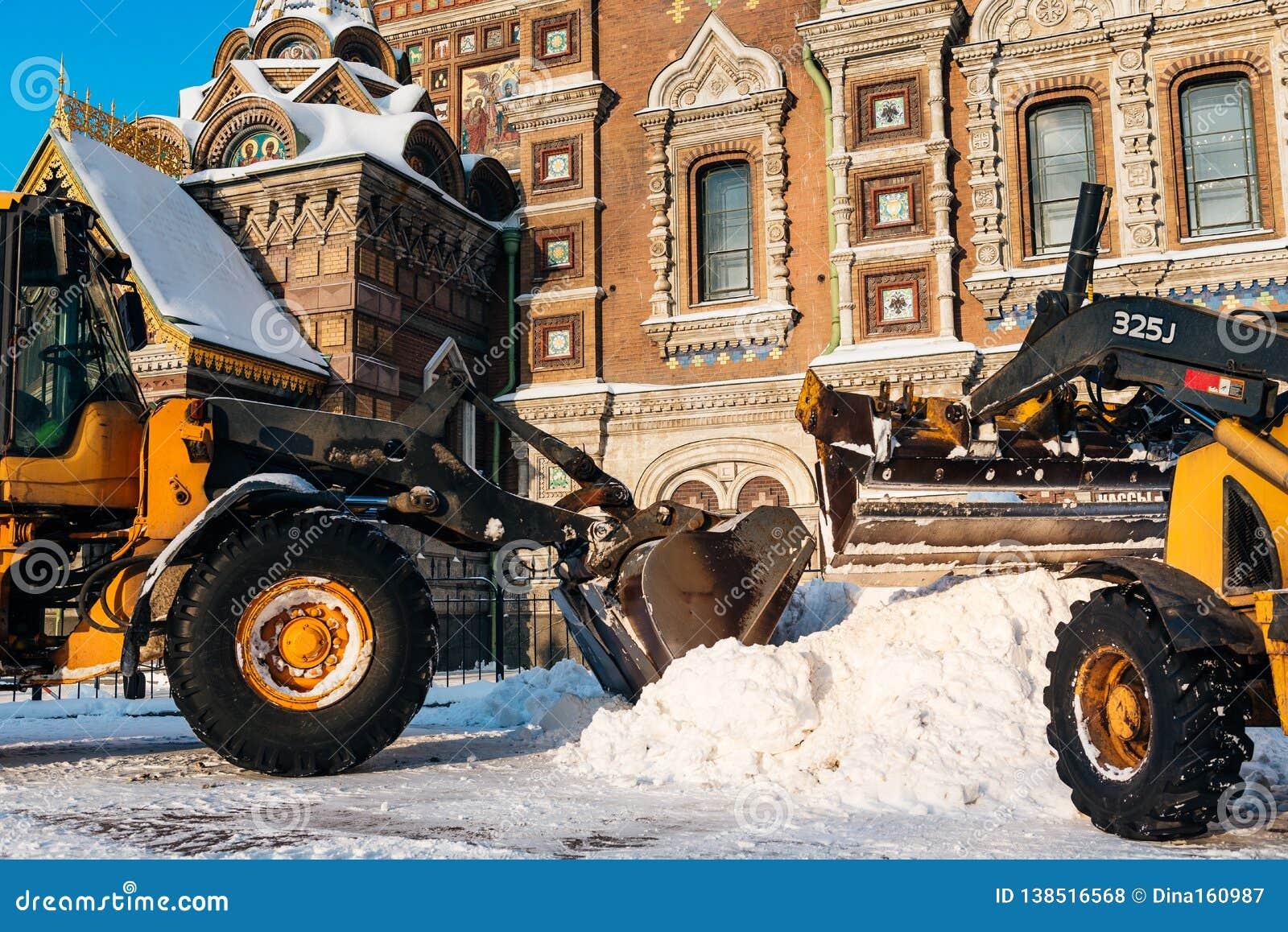 Корабль удаления снега извлекая снег Трактор освобождает путь после сильного снегопада в Санкт-Петербурге, России