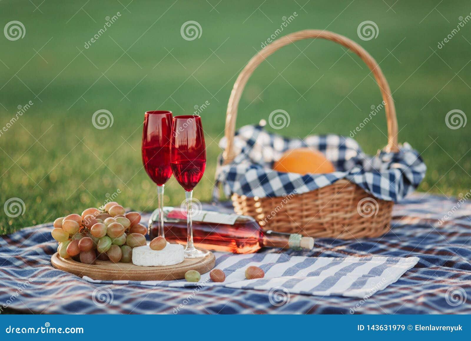 Корзина пикника с напитками, едой и плодом на снаружи зеленой травы в парке лета