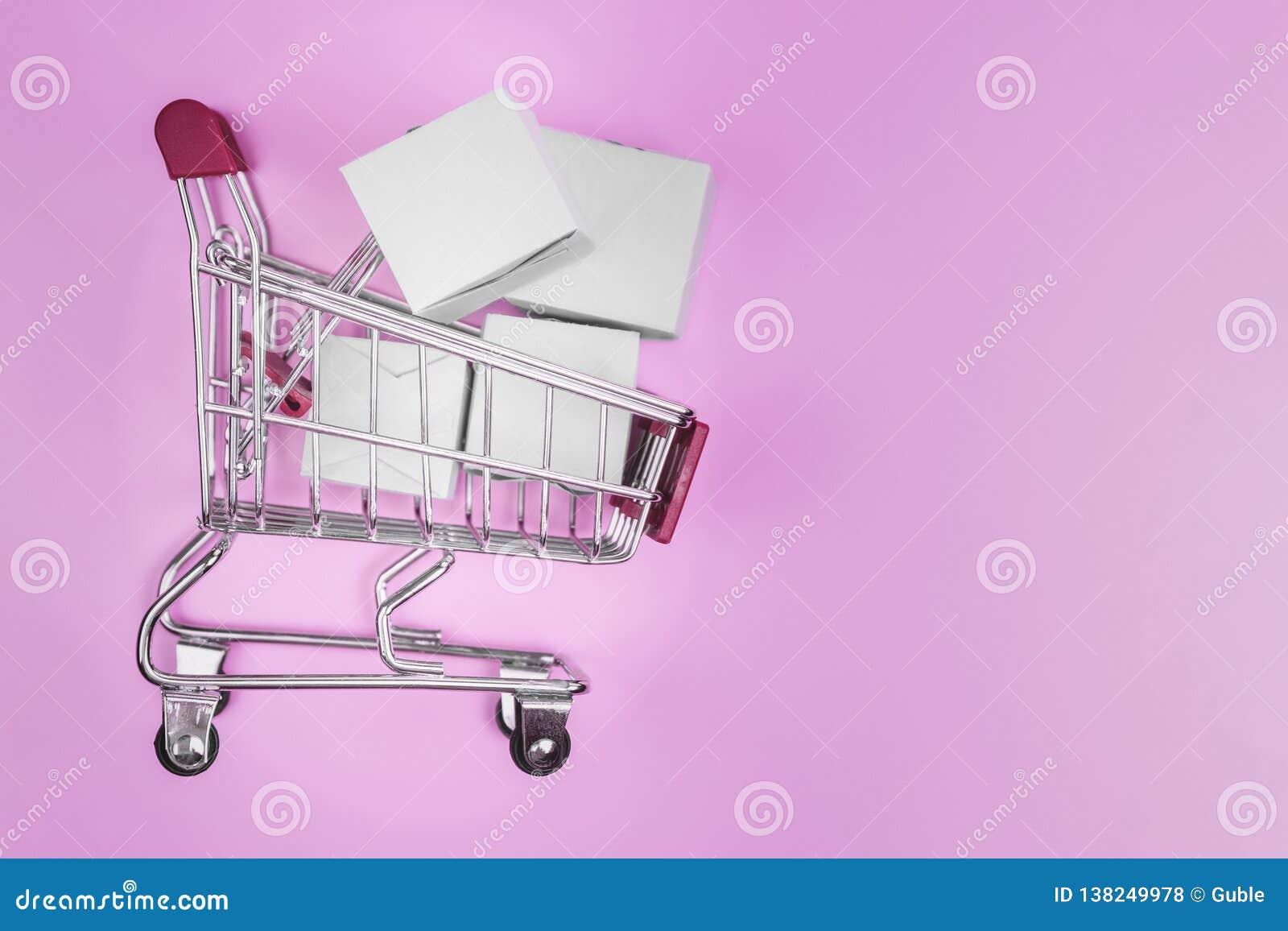 Корзина с коробками на розовой предпосылке Концепция поставлять и онлайн магазина