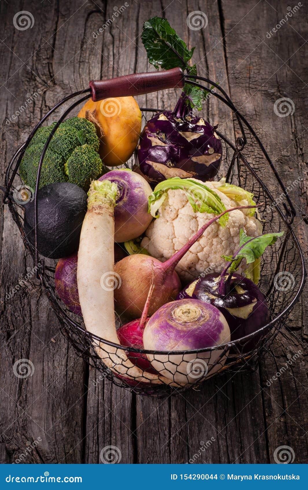 Корзина с овощами на деревянной предпосылке Цветная капуста, брокколи, редиска, пастернак, лук-порей, кольраби