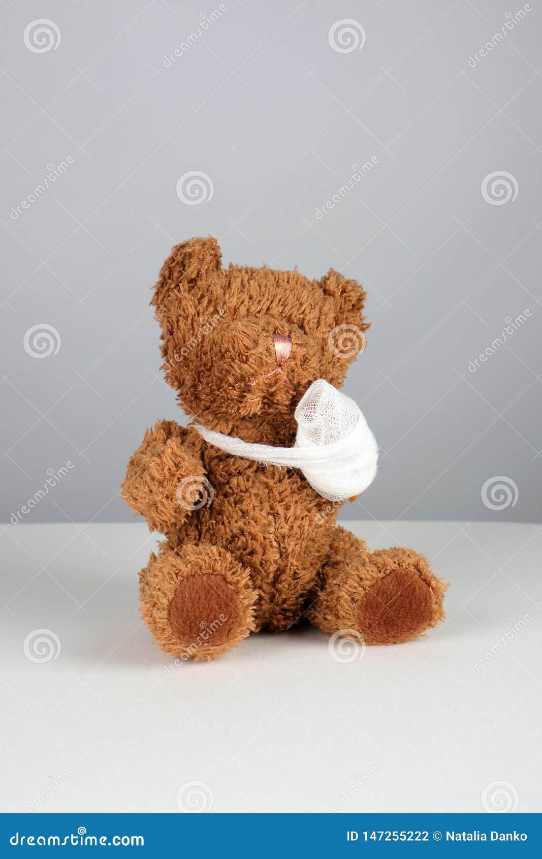 коричневая плюшевый мишка с перевязанной лапкой