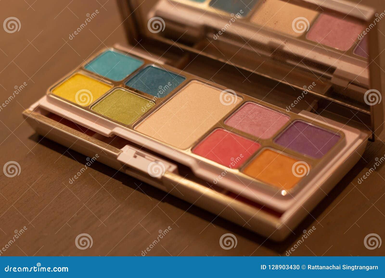 Косметическая коробка порошка установила много цвет на деревянном столе