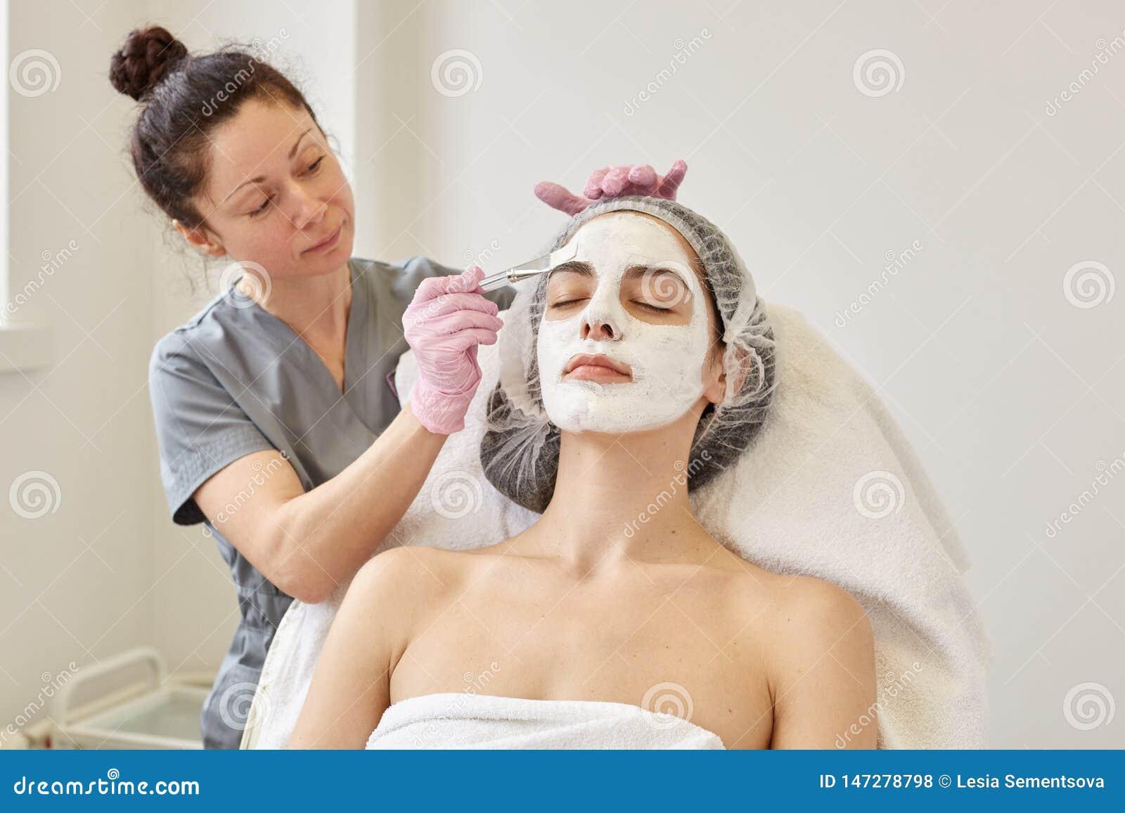 Косметическая процедура спа, концепция skincare Женщина получая лицевую заботу beautician на салоне спа, слезать стороны applays