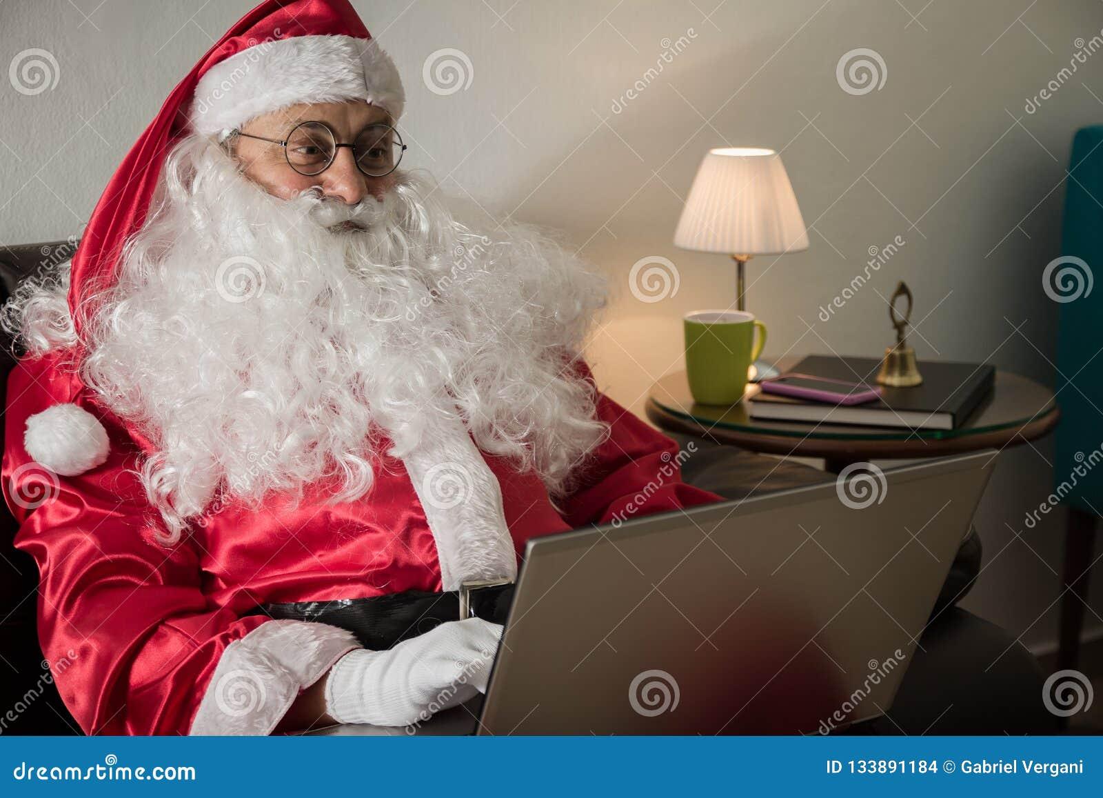 Косой Санта Клауса ослабляя в софе дома используя ноутбук fo