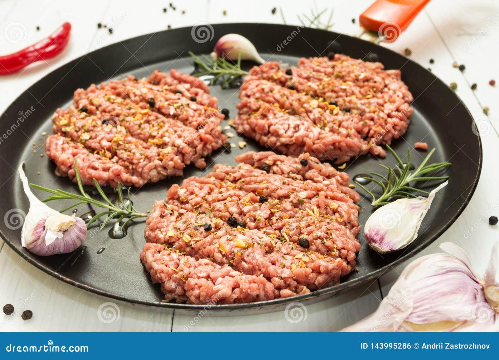 Котлеты органической говядины сырцовые со специями в сковороде на белой предпосылке с чесноком, розмариновым маслом и перцем