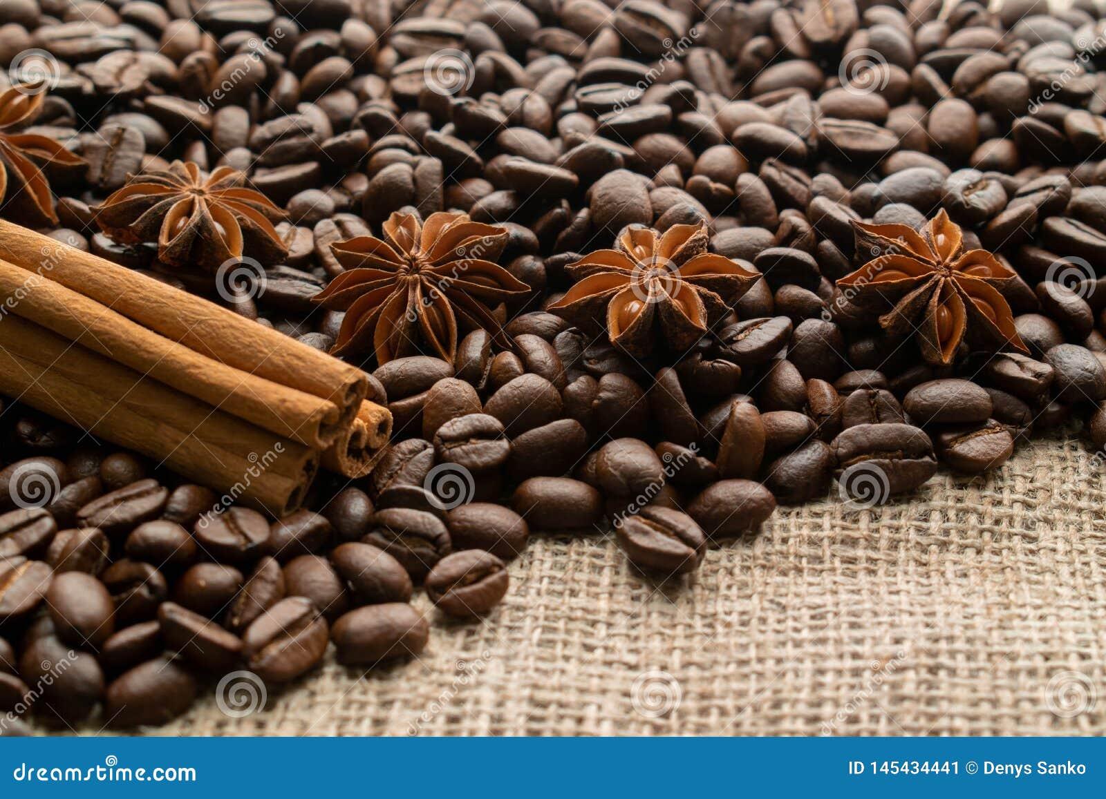 Кофе всей фасоли с aniseas звезды и ручками циннамона на светлой мешковин
