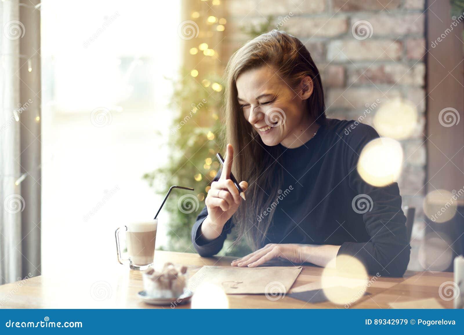 Кофе красивого смеха молодой женщины выпивая в ресторане кафа, портрете смеяться над счастливой дамой около окна Праздники призва