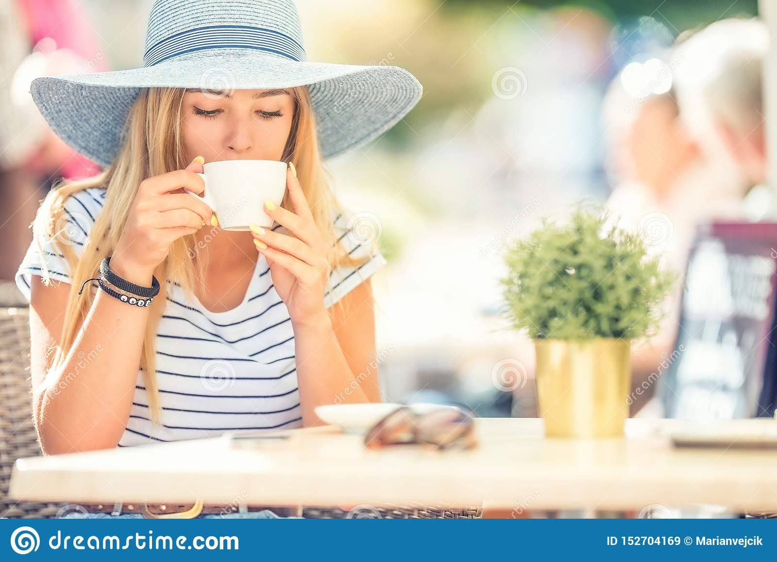 Кофе красивой девушки выпивая в террасе кафа Молодая женщина портрета лета
