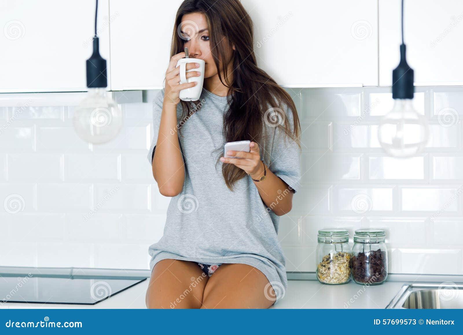 Кофе красивой молодой женщины выпивая и использование ее мобильного телефона