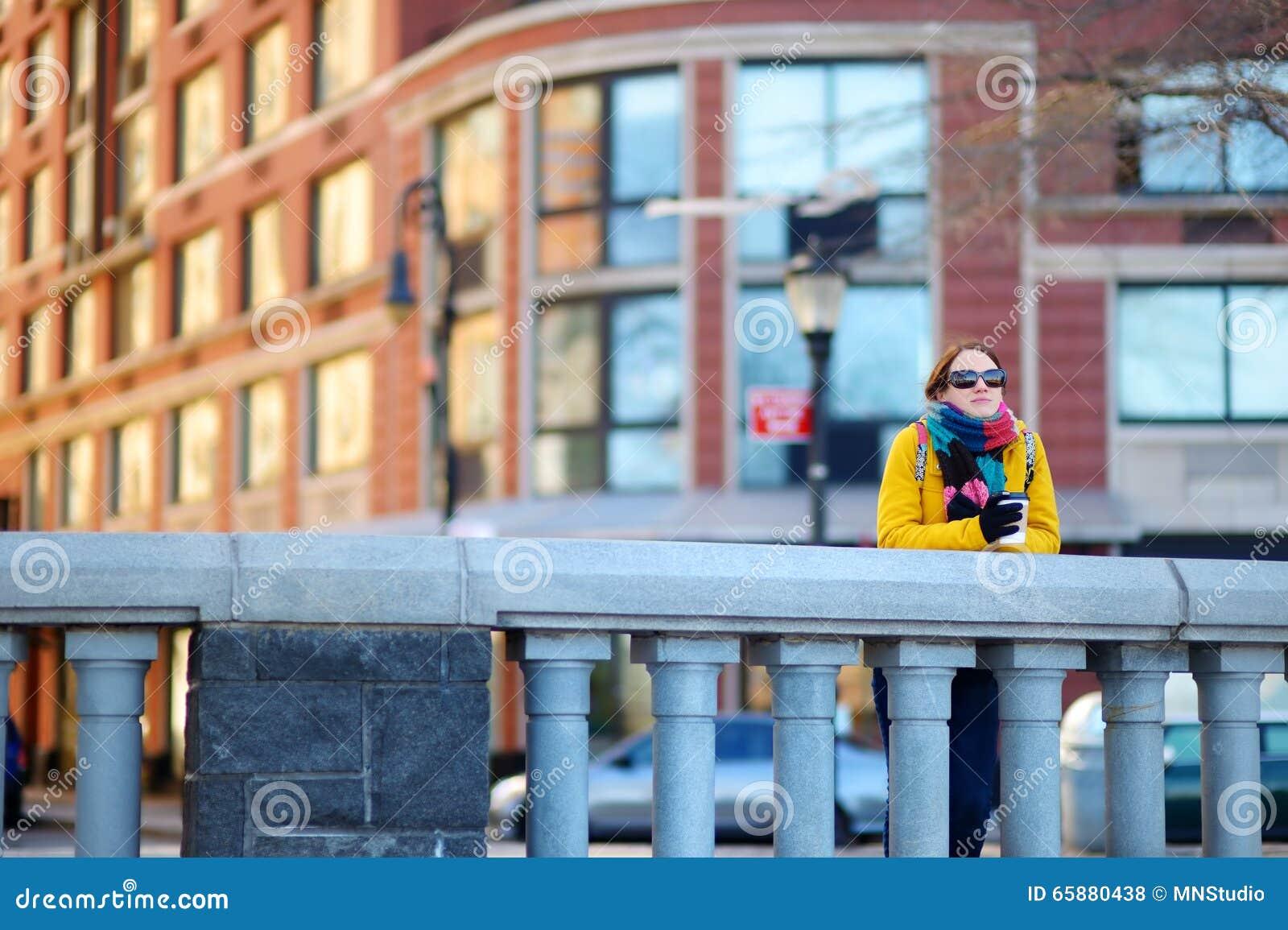 Кофе красивой молодой женщины выпивая на солнечный весенний день в Нью-Йорке