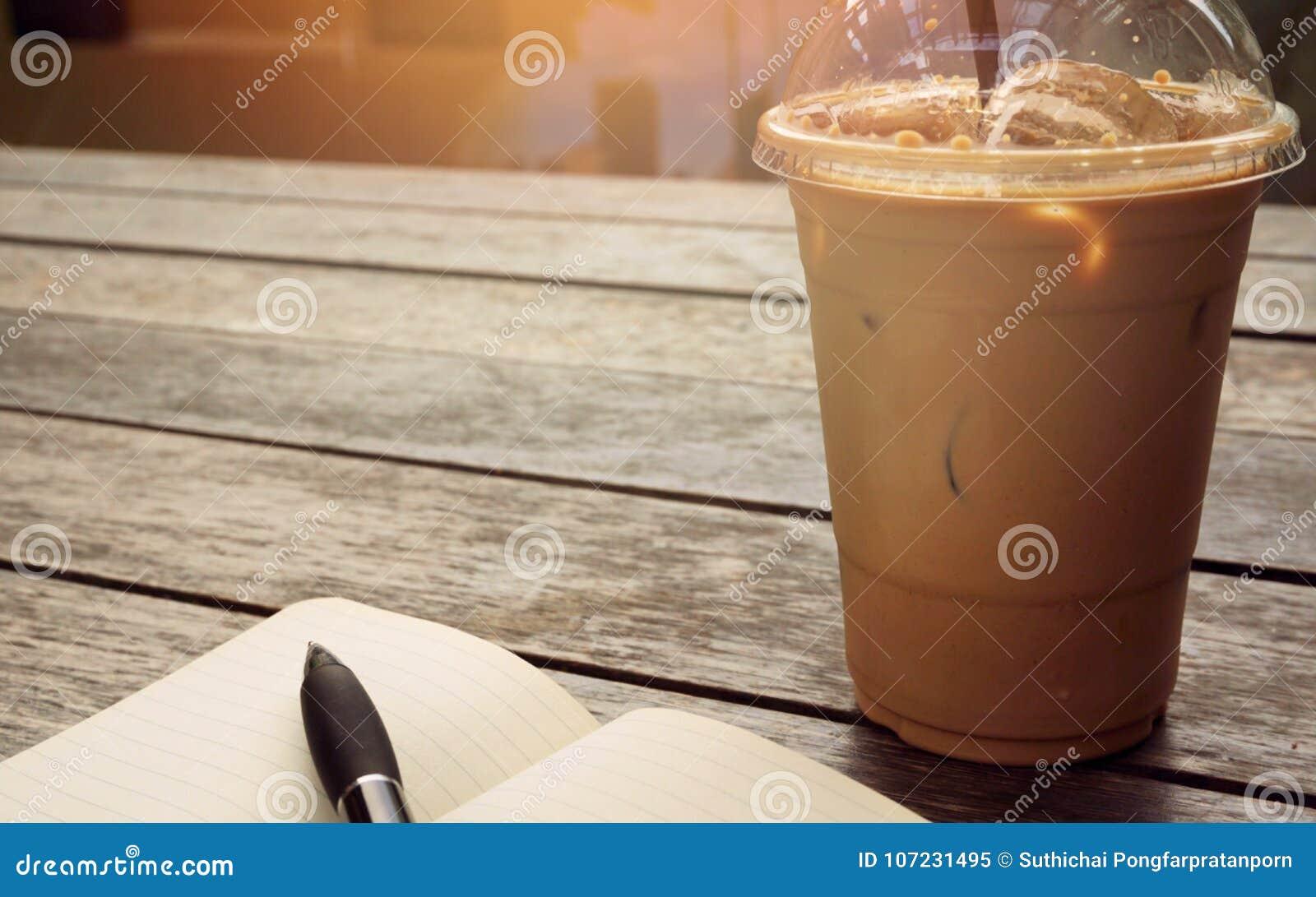 Кофе льда в на вынос чашке с тетрадью и ручка на стороне Bo