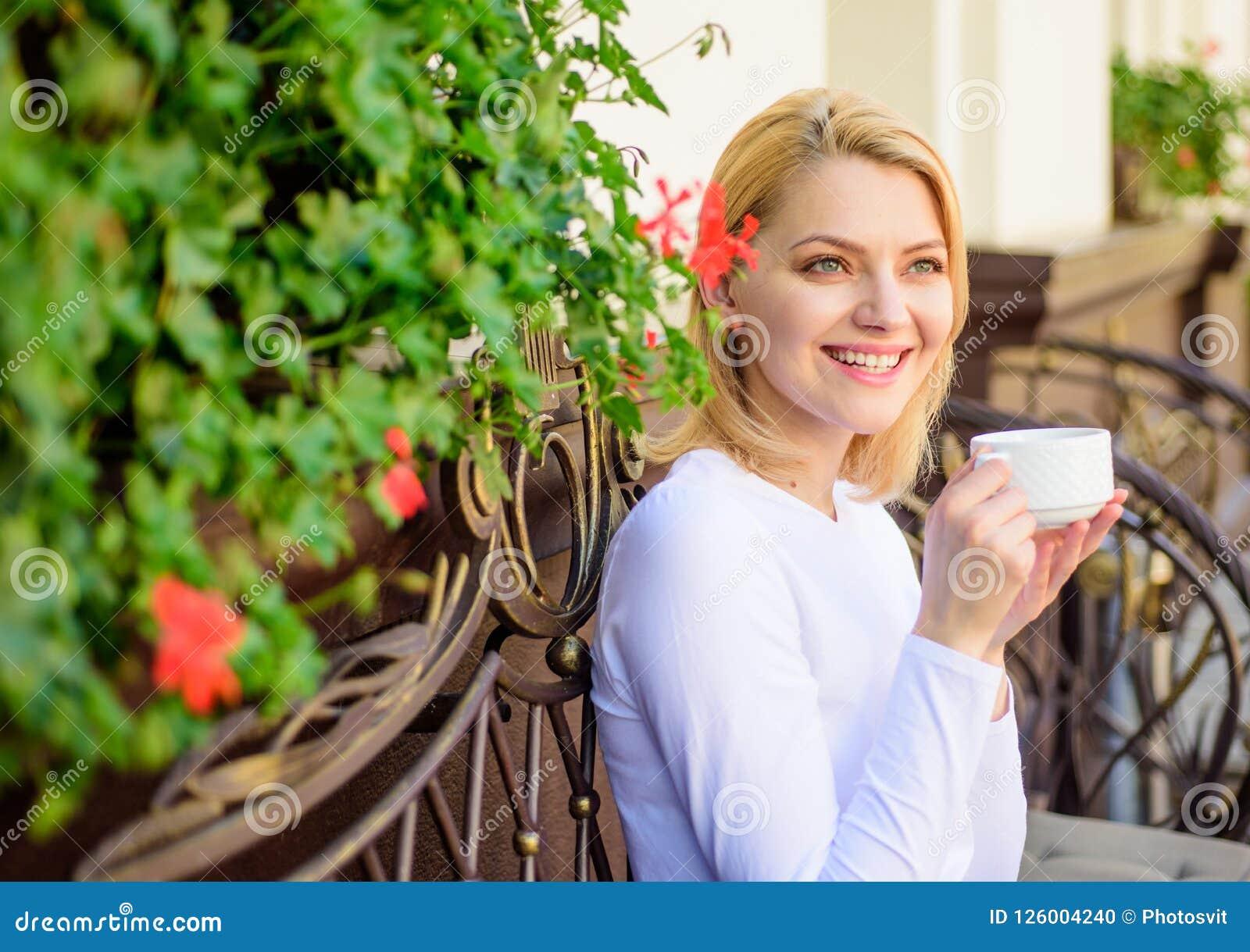 Кофе питья девушки каждое утро на том самом месте как ежедневно ритуал Женщина имеет террасу кафа питья outdoors Имейте глоточек