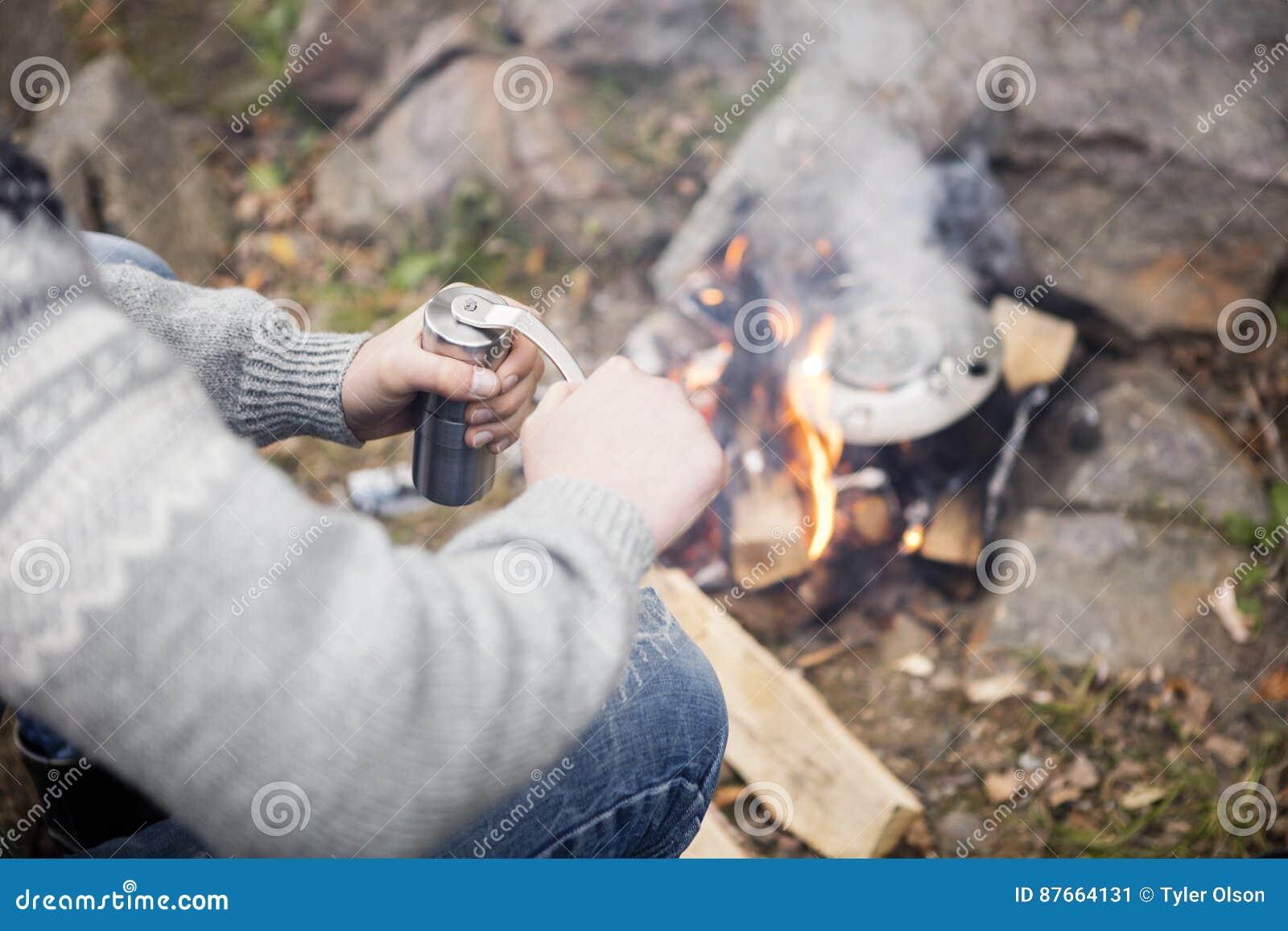 Кофе человека меля около костра на месте для лагеря