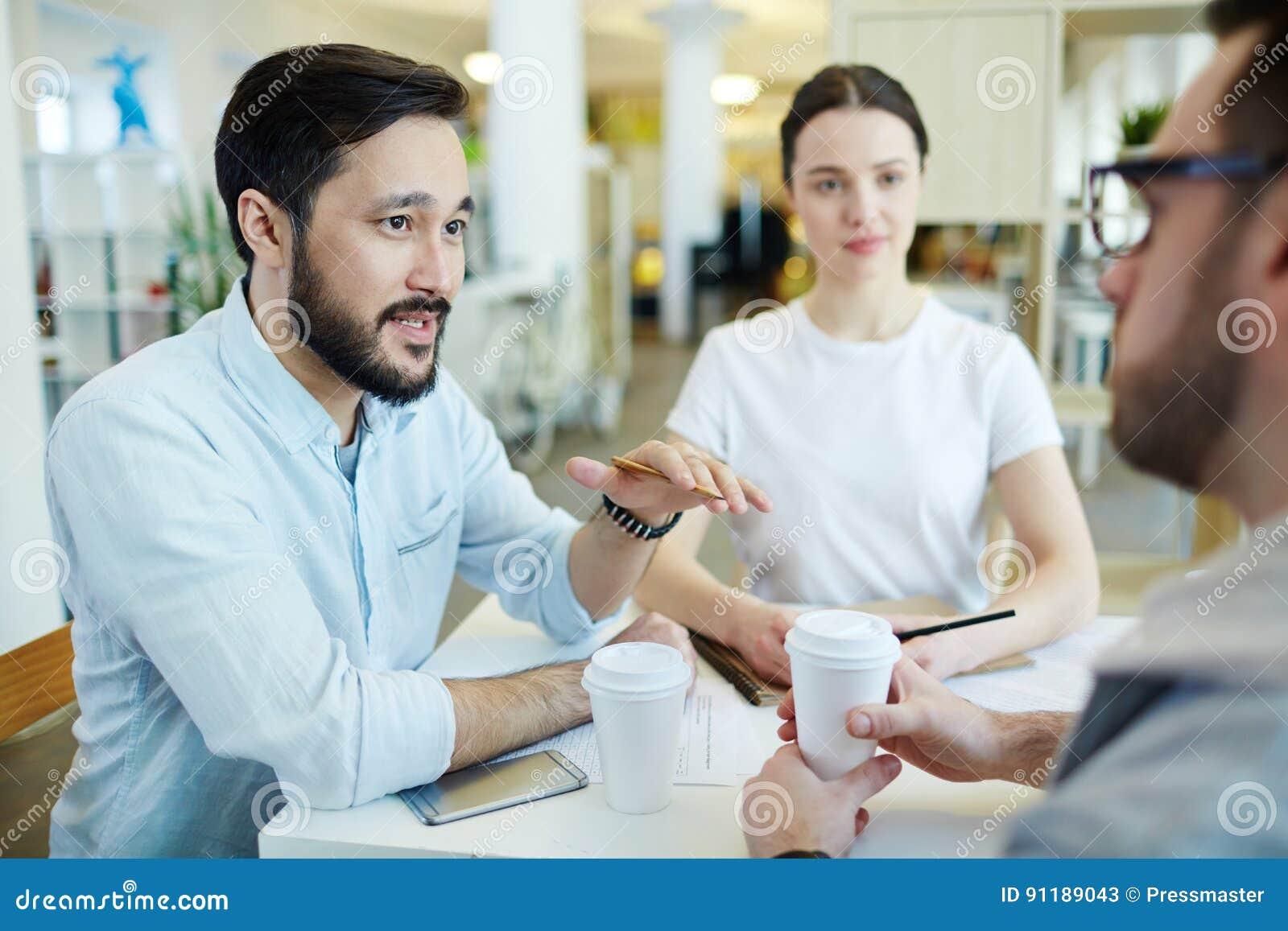 Коллеги обсуждая работу на перерыв на ланч
