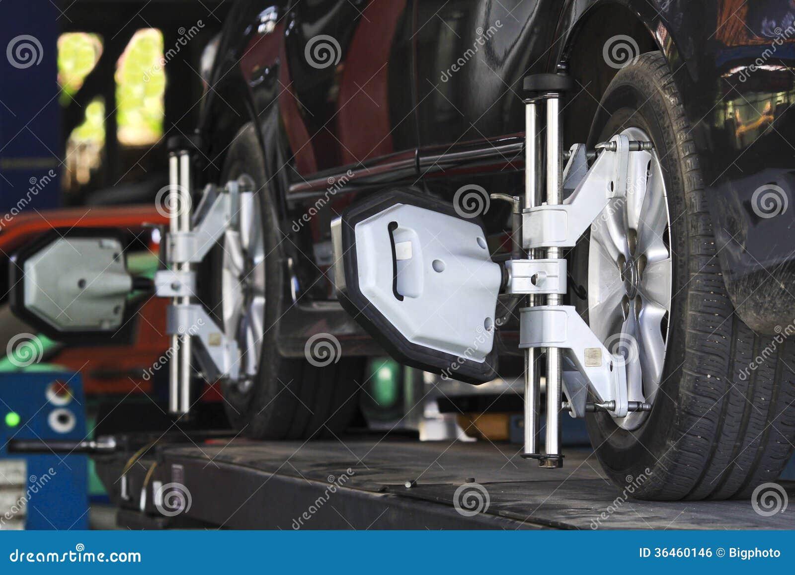 Колесо автомобиля зафиксированное с компьютеризированной струбциной машины выравнивания колеса