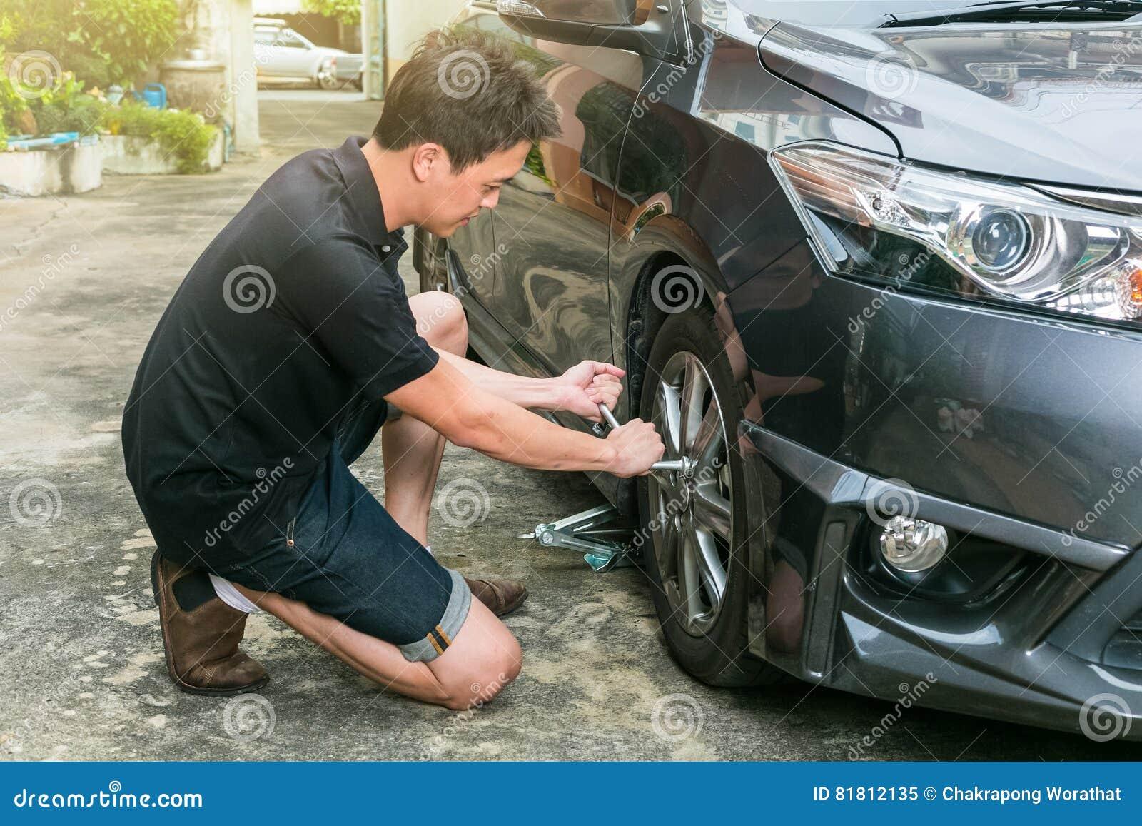 Колесо молодого человека изменяя его автомобиля на дороге