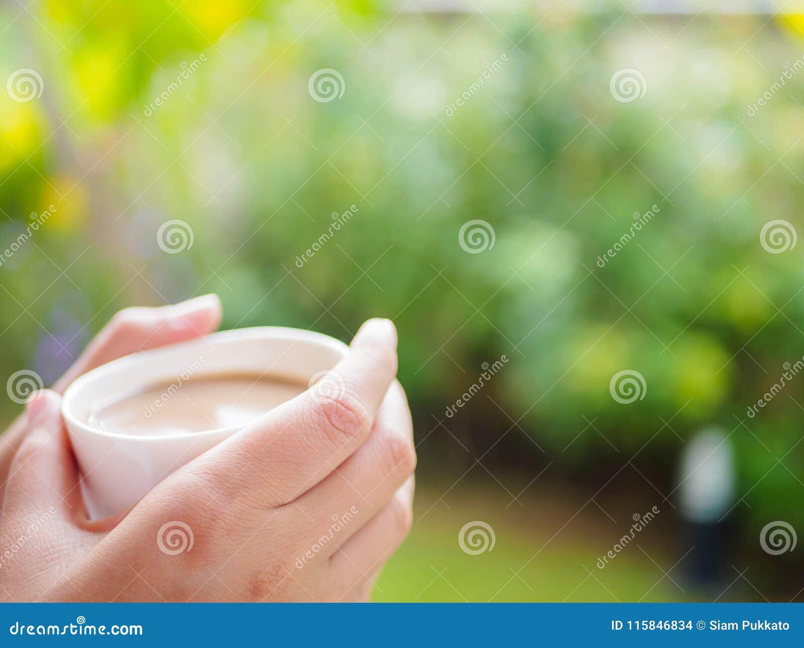 Красивая азиатская женщина выпивая чашку кофе на саде