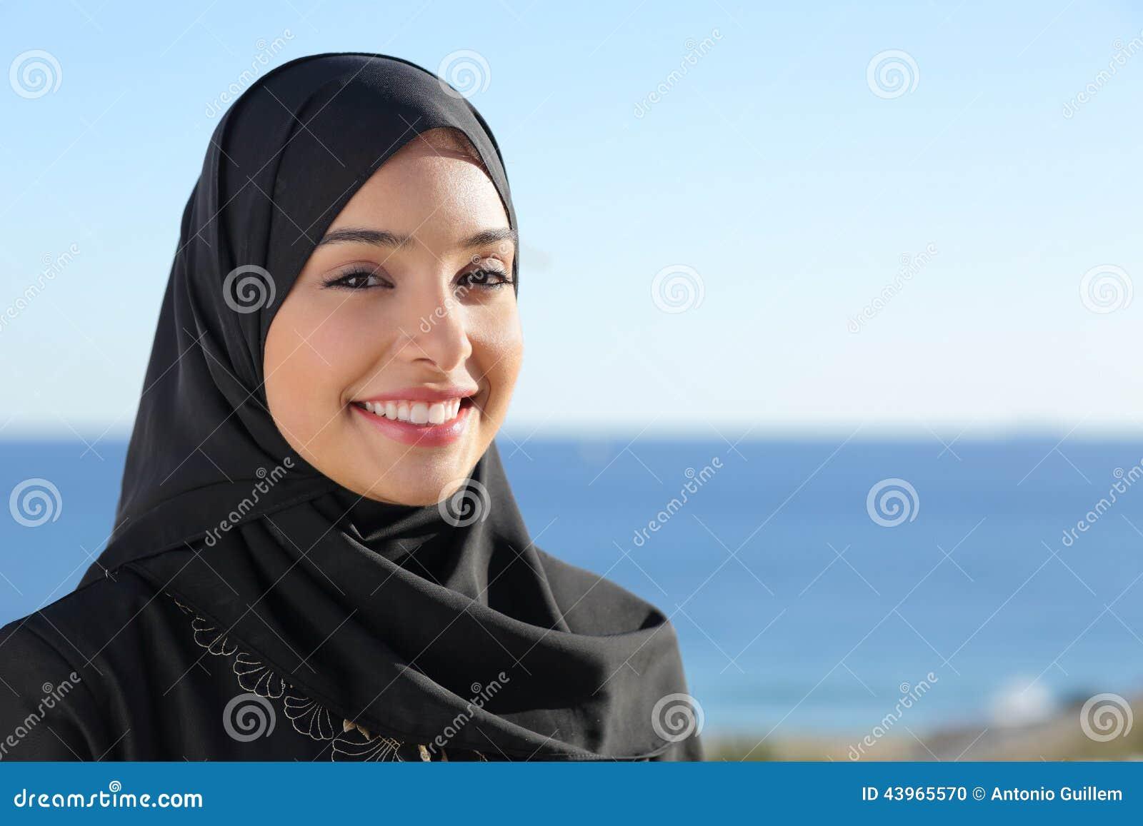 Красивая арабская саудовская сторона женщины представляя на пляже