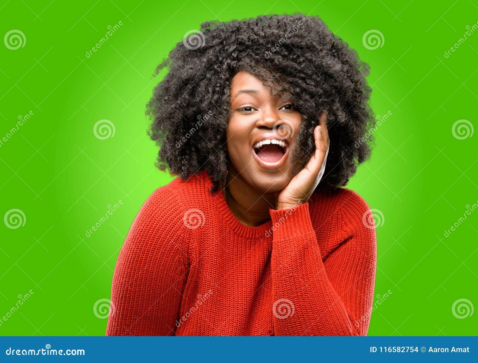 Красивая африканская женщина при вьющиеся волосы изолированное над зеленой предпосылкой