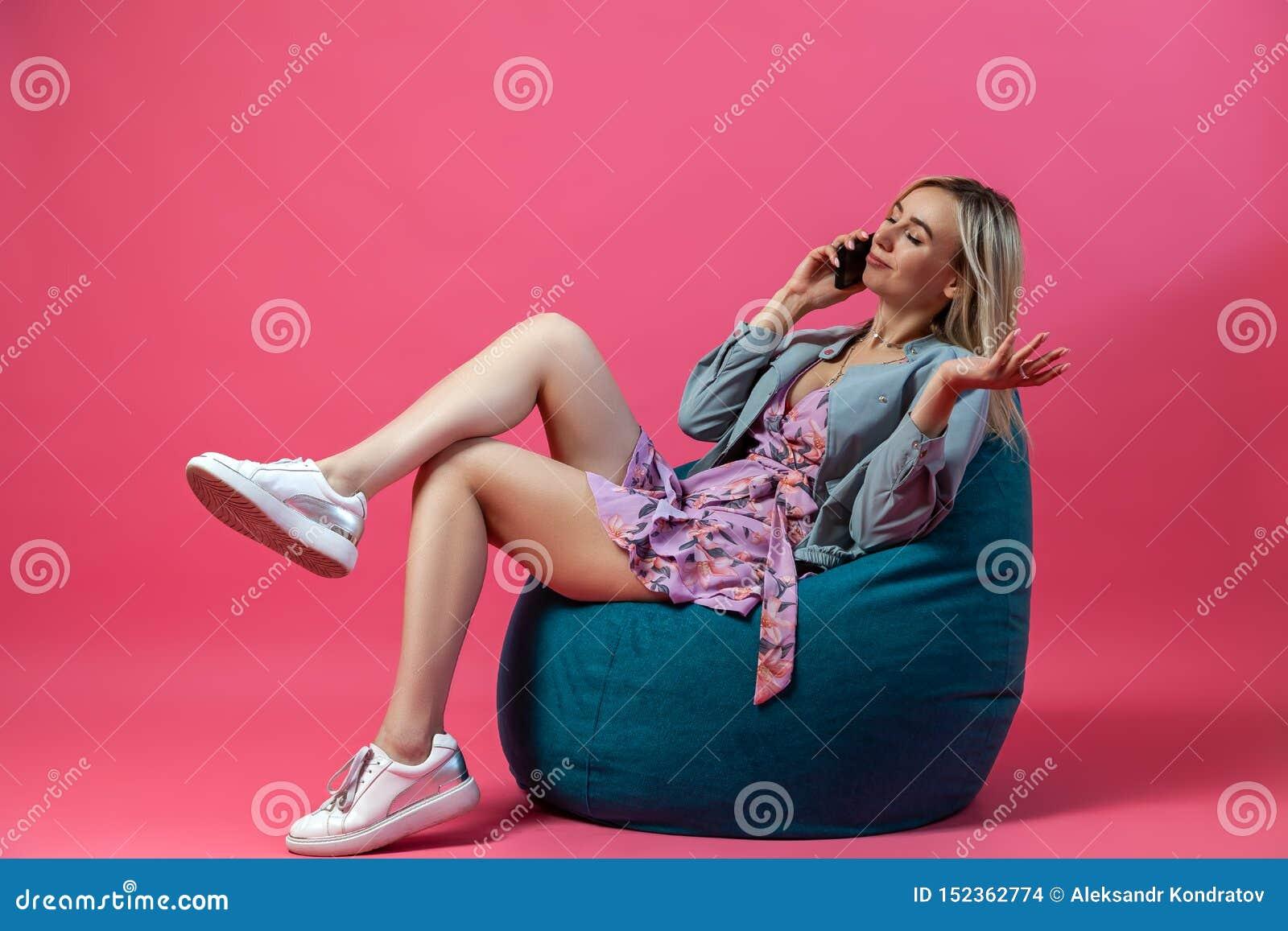 Красивая белокурая девушка в синем пиджаке и пурпурные sundress сидит на зеленом изолированном стуле сумки с ее ногами сложенными