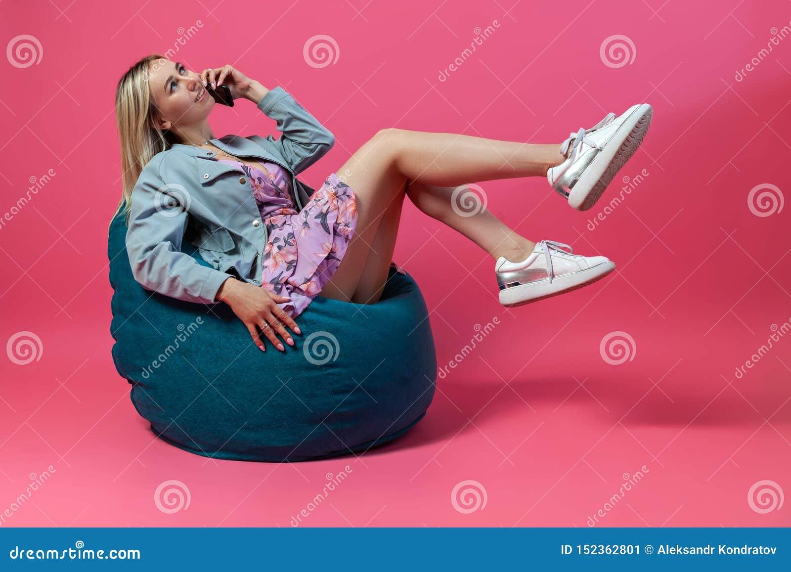 Красивая белокурая девушка в синем пиджаке и пурпурные sundress сидит на зеленом стуле сумки с ее поднимаясь изолированными ногам