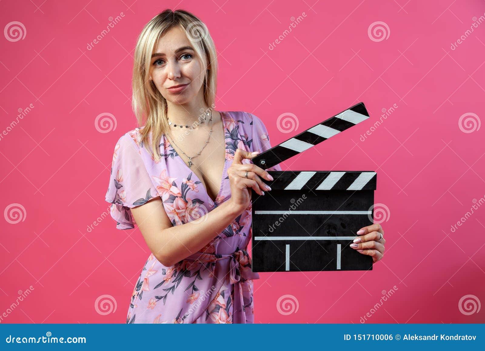 Красивая белокурая женщина в пурпурные sundress держит открытый кинорежиссер clapperboard в черноте с белыми нашивками для начала