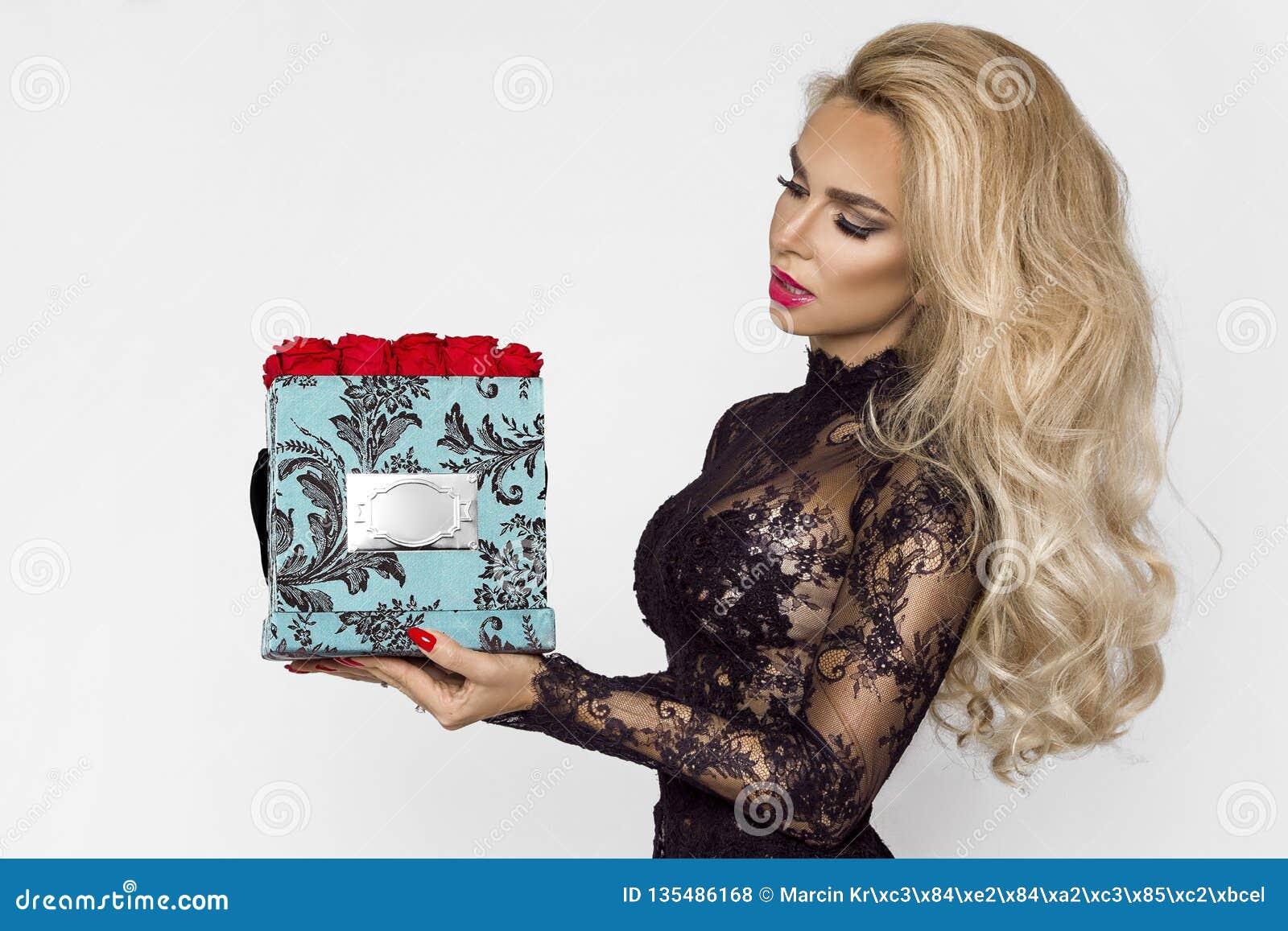 Красивая белокурая модель в элегантном длинном платье держа присутствующую коробку с розами