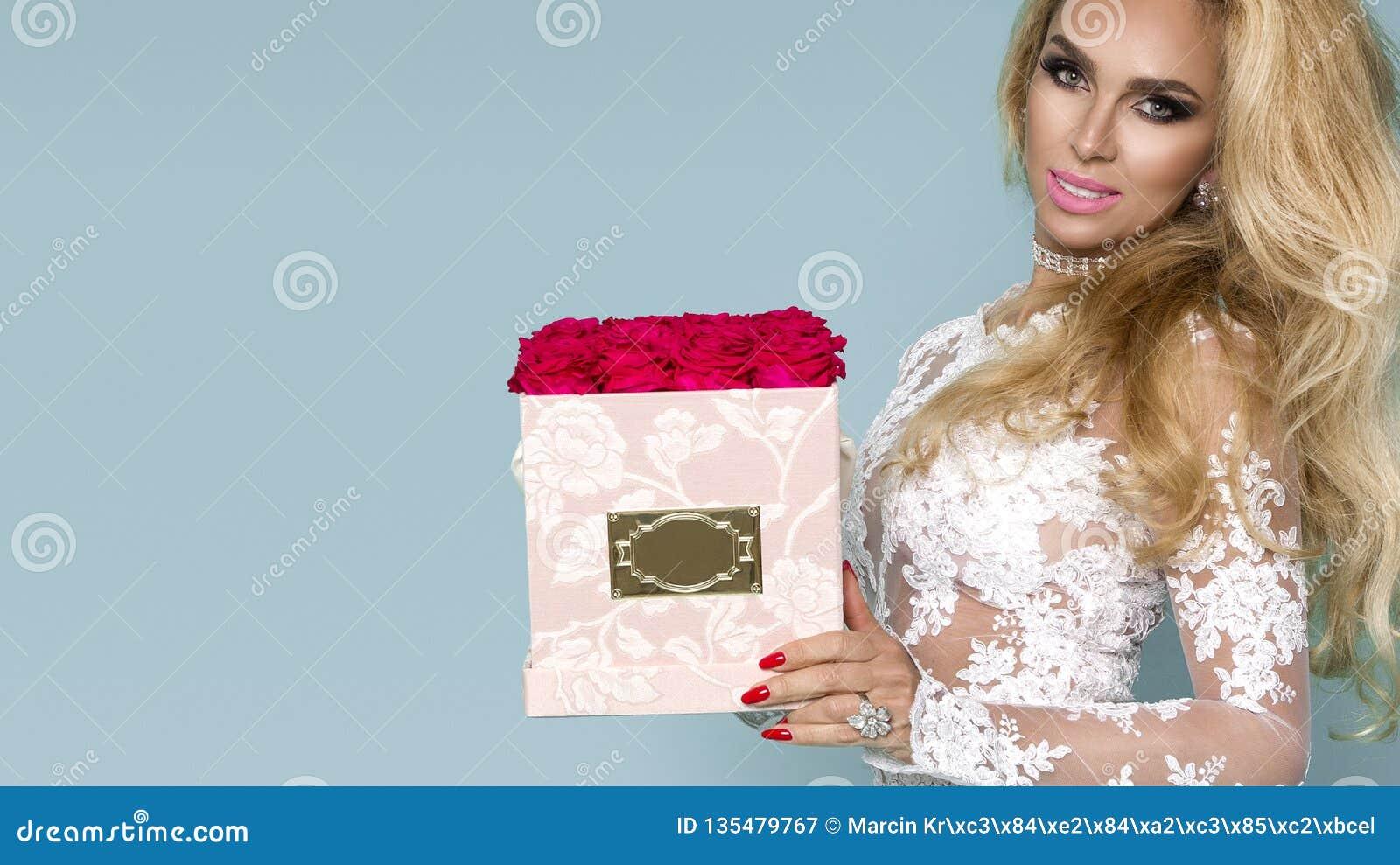 Красивая белокурая модель в элегантном платье держа букет роз, коробку цветка Валентайн и подарок на день рождения на голубой пре