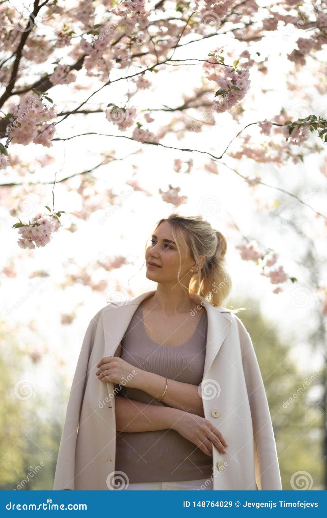 Красивая белокурая молодая женщина в парке вишневого цвета Сакуры весной наслаждаясь природой и свободным временем во время ее пу