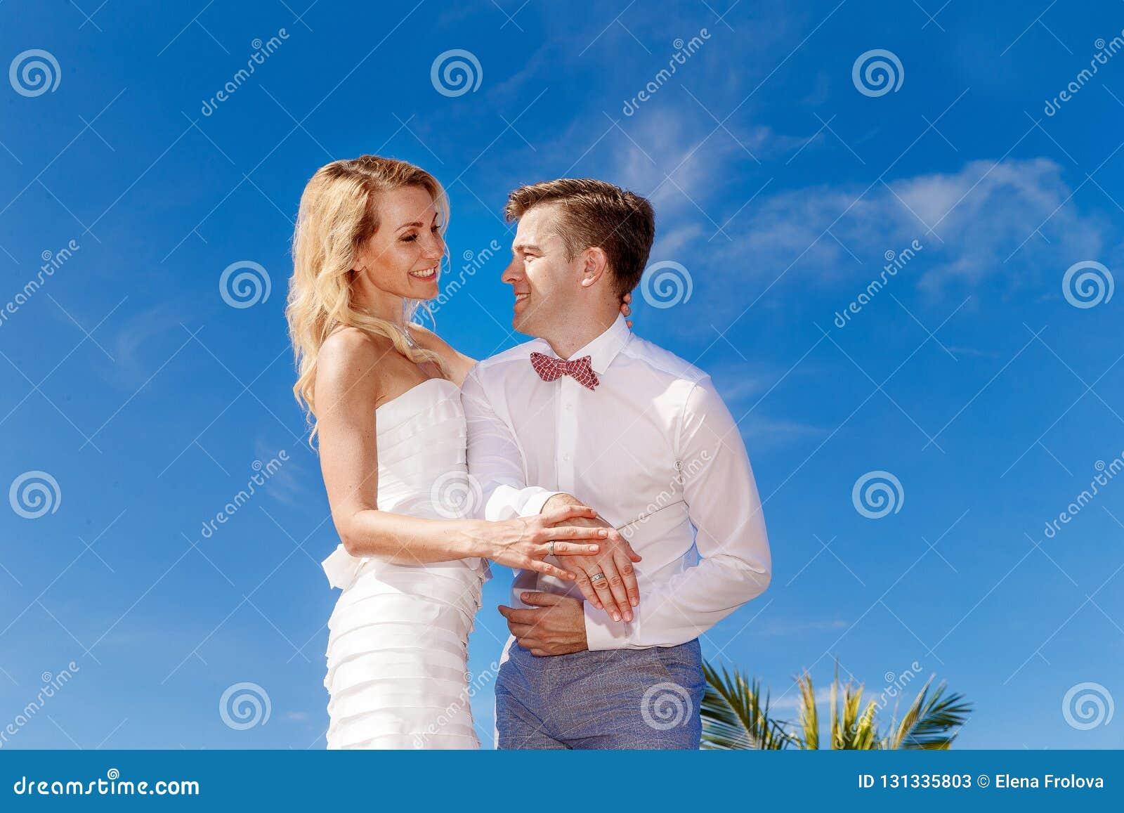 Красивая белокурая невеста в белых платье и groom свадьбы вручает sh