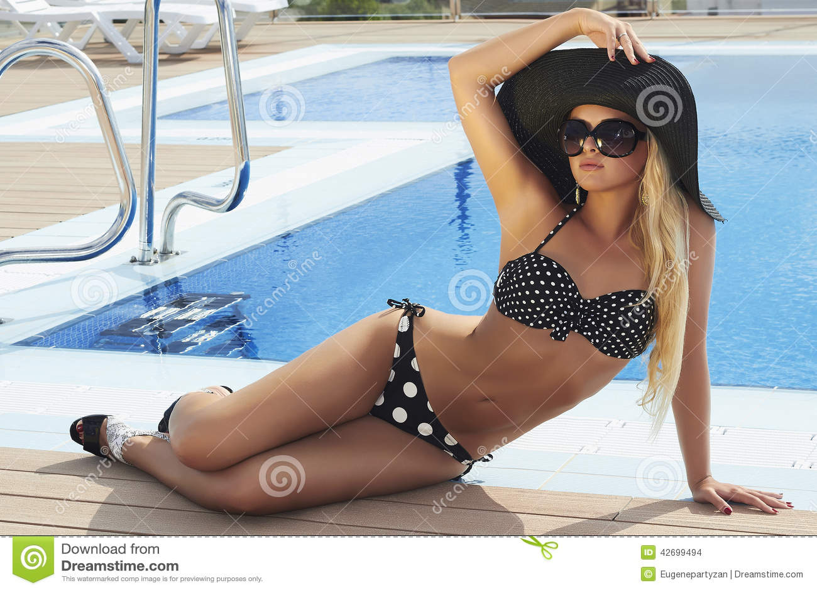 Красивая белокурая женщина в солнечных очках приближает к бассейну Лето Девушка в Бикини женщина шлема сексуальная