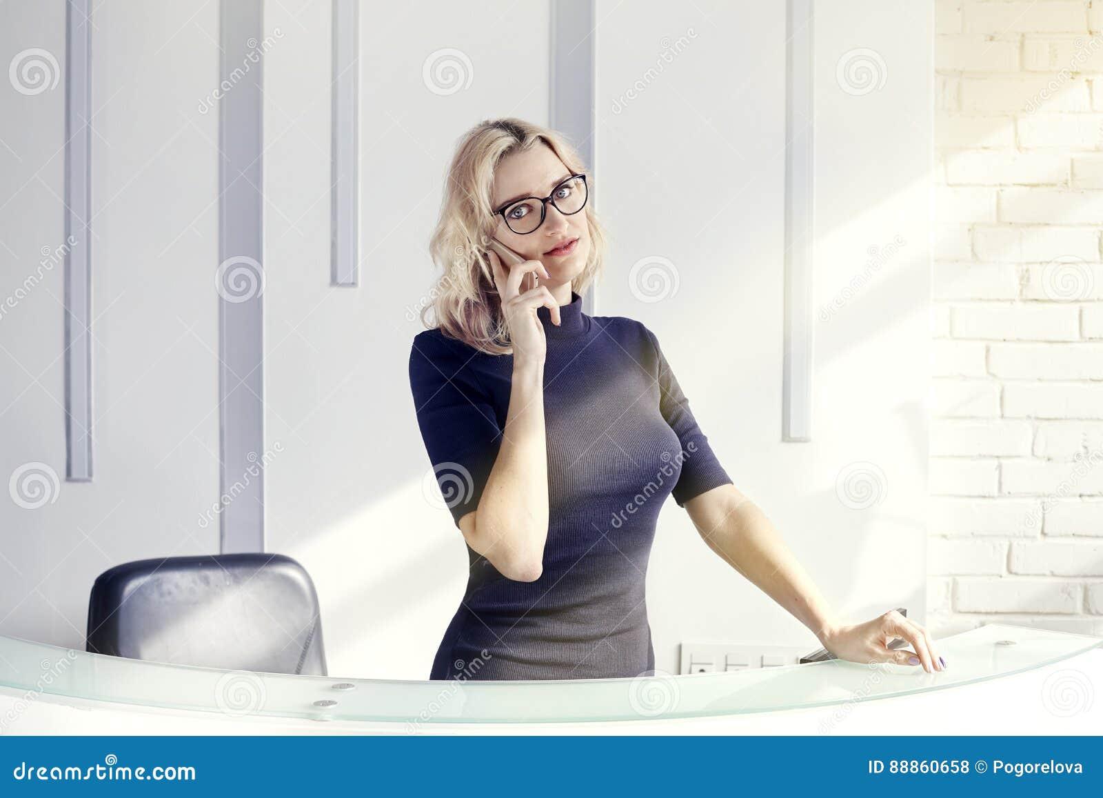 Красивая белокурая дружелюбная женщина за приемной, администратор говоря телефоном Солнечность в современном офисе