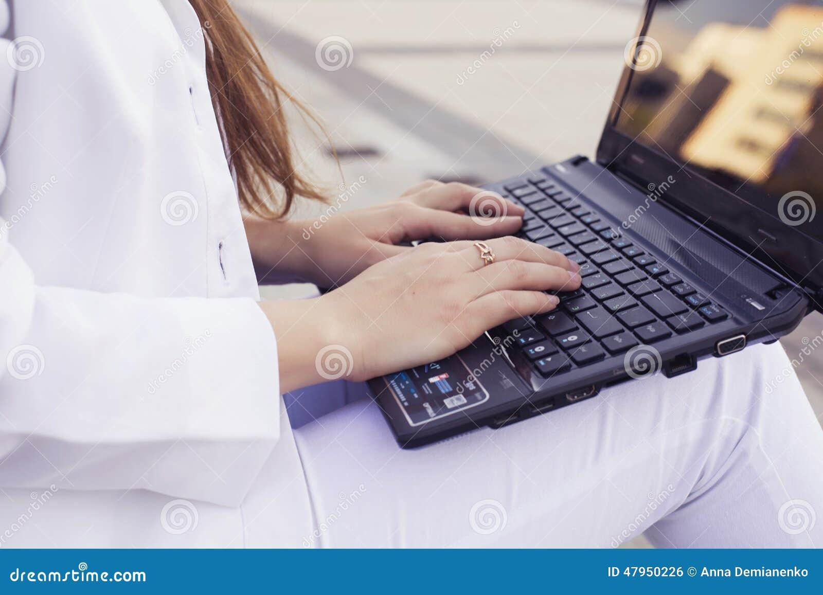 Красивая бизнес-леди брюнет в белом костюме с тетрадью на ее подоле, печатать, работая outdoors Руки на конце клавиатуры вверх