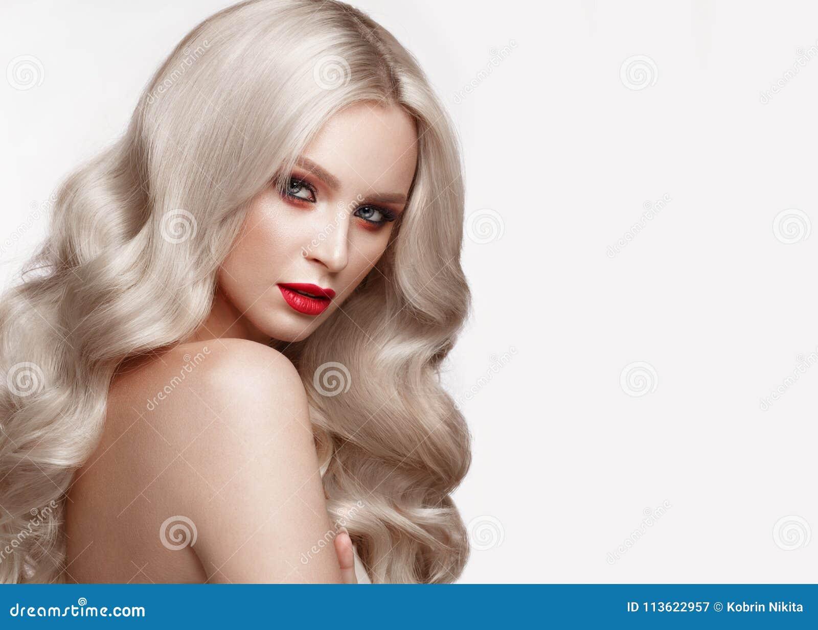 Красивая блондинка в образе Голливуда с скручиваемостями, естественным составом и красными губами Сторона и волосы красотки