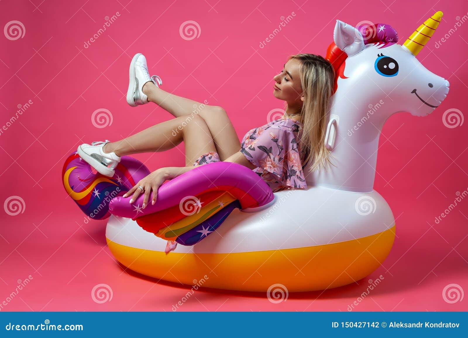 Красивая блондинка женщины в сексуальные sundress в белых тапках сидит поднимающ ее ноги вверх на раздувном пестротканом единорог