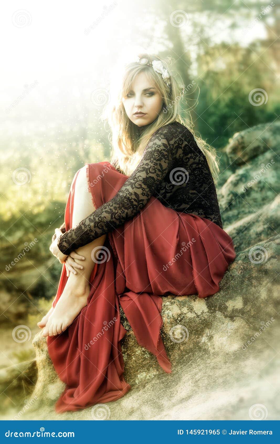 Красивая блондинка феи одетая в красном усаживании на roccks