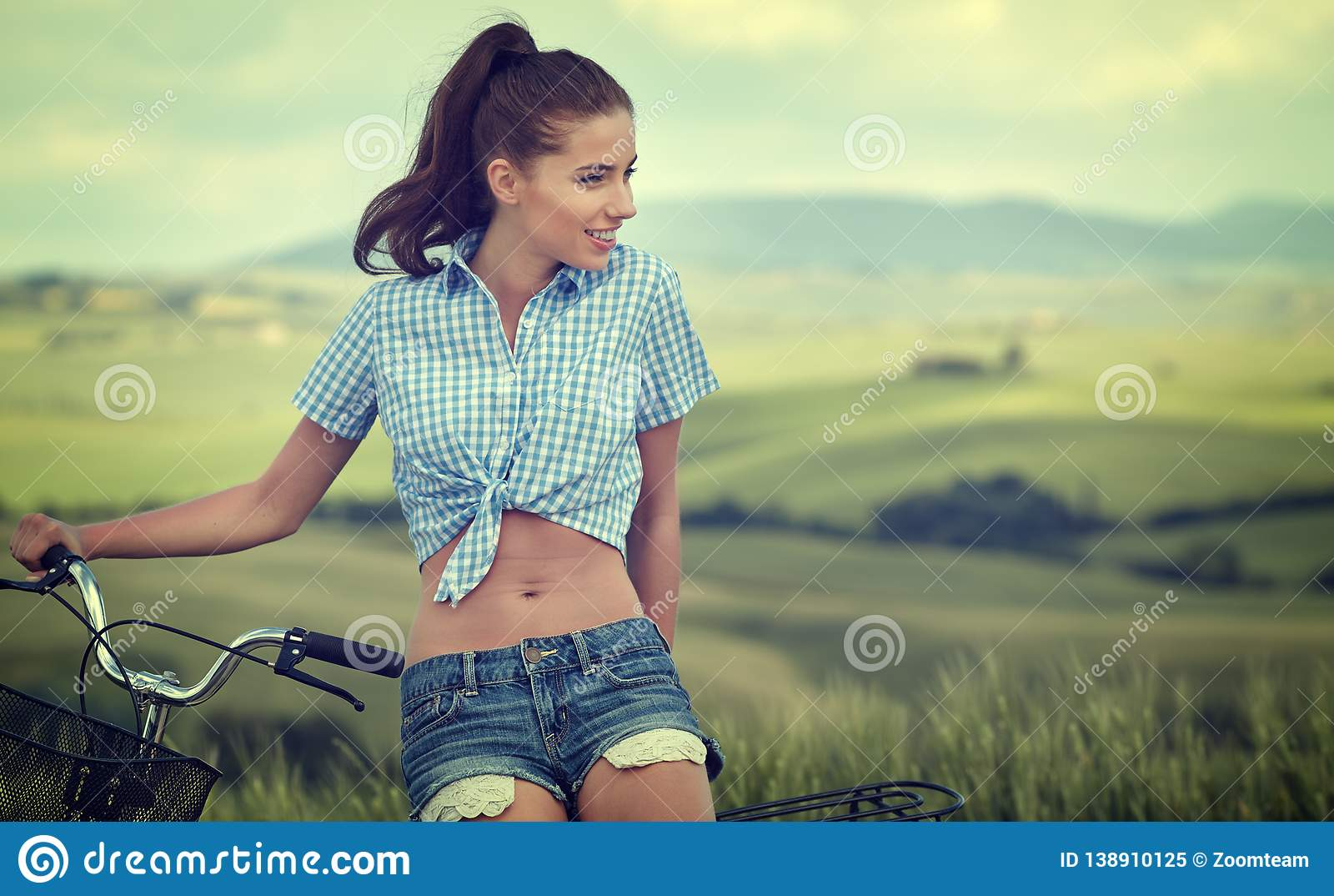 Красивая винтажная девушка сидя рядом с велосипедом, летом