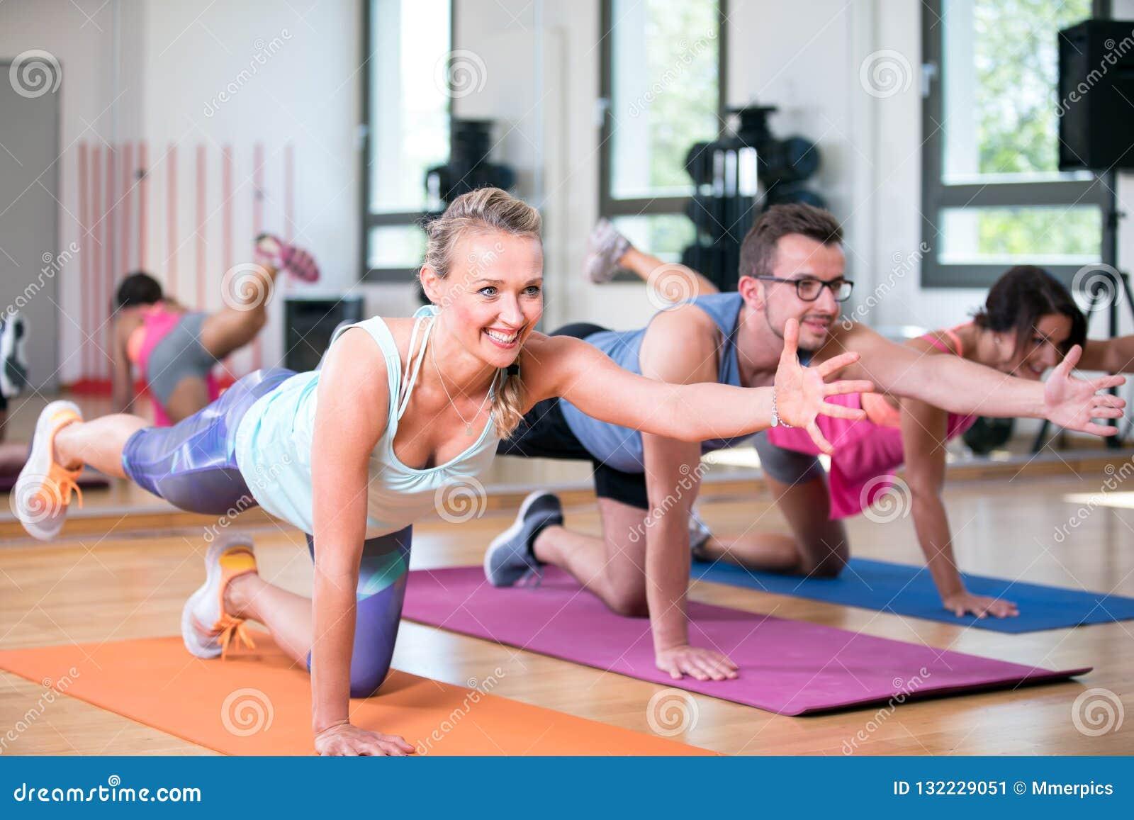 Красивая группа человека женщин делает разминку фитнеса спорта в спортзале