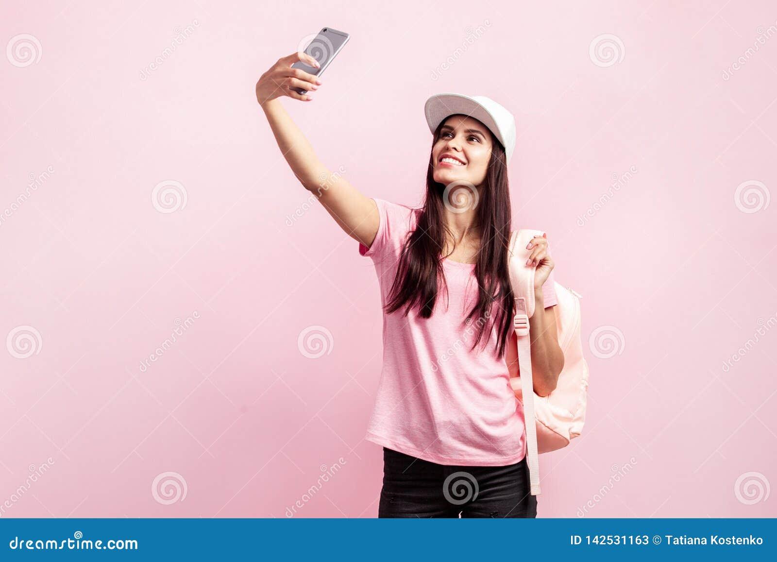 Красивая девушка в белой крышке и с рюкзаком на ее плечах одетых в розовой футболке и черных джинсах делает selfie